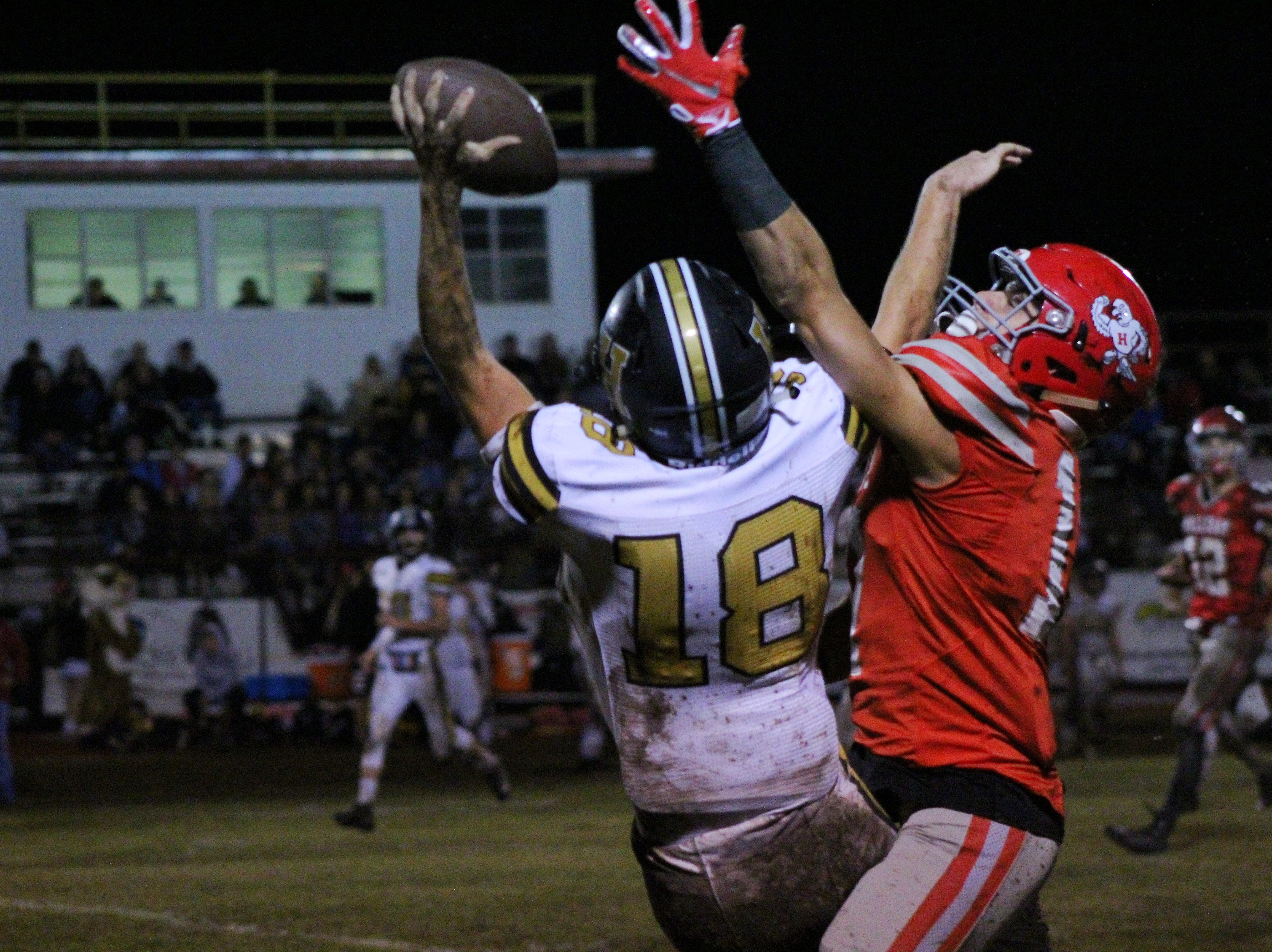 Holliday's Cole Harrison and Henrietta's Weston Dowell battle for a pass. Both teams emphasized rushing rather than passing tonight at the slippery grass stadium in Holliday.