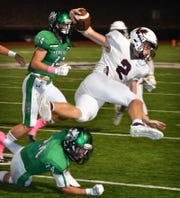 Vernon Lions quarterback BT White (2) goes airborne from a hit by Iowa Park's Kaden Ashlock (24) in second quarter action Friday night in Iowa Park.