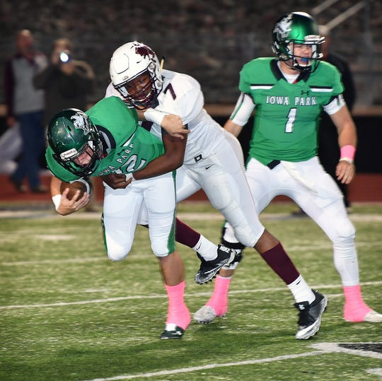 Iowa Park's Reid Lalk (12) is hit immediately after taking a handoff from quarterback Trent Green (1) as Vernon's Martavious McFarland (7) reads the play Friday night in Iowa Park.