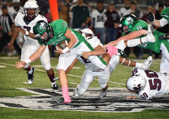 Iowa Park senior Reid Lalk (12) struggles for extra yardage as several Vernon Lions defenders move in for the tackle during Friday night's game in Iowa Park.