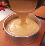 The the batter for pumpkin Cheesecake is added to the springform pan on top of graham cracker crust.