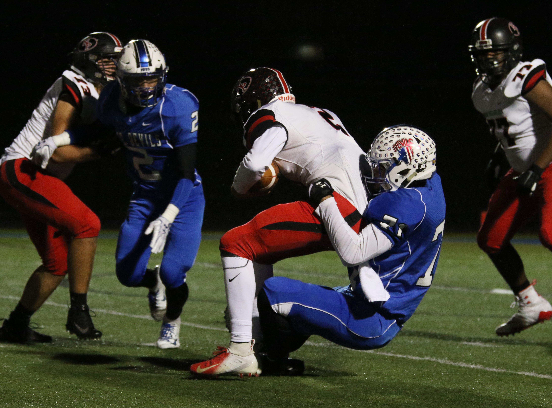 Zanesville's Kaden C. Mayle pulls down New Philadelphia quarterback Baron May.