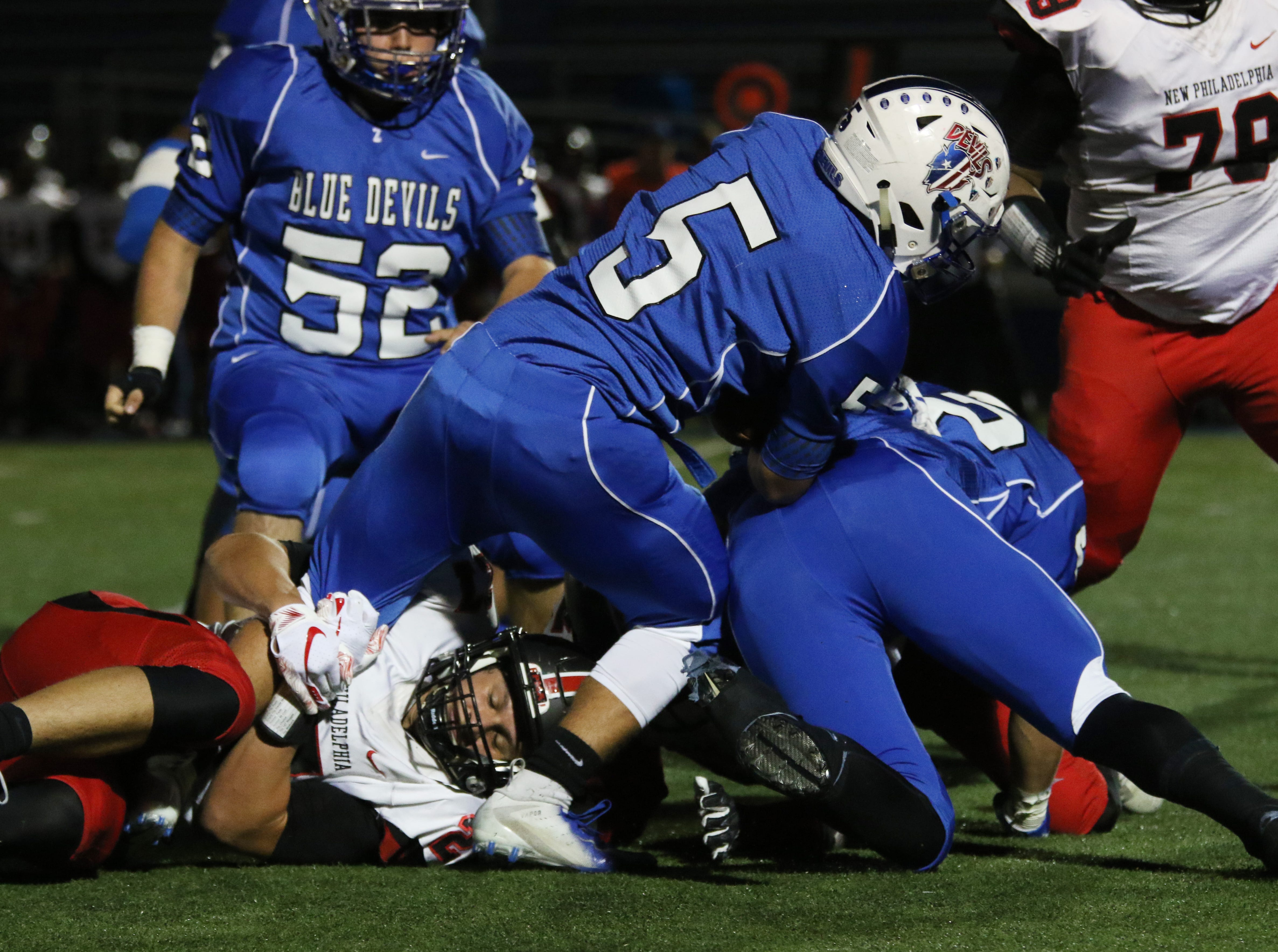Zanesville's JC Curtis carries the ball against New Philadelphia.