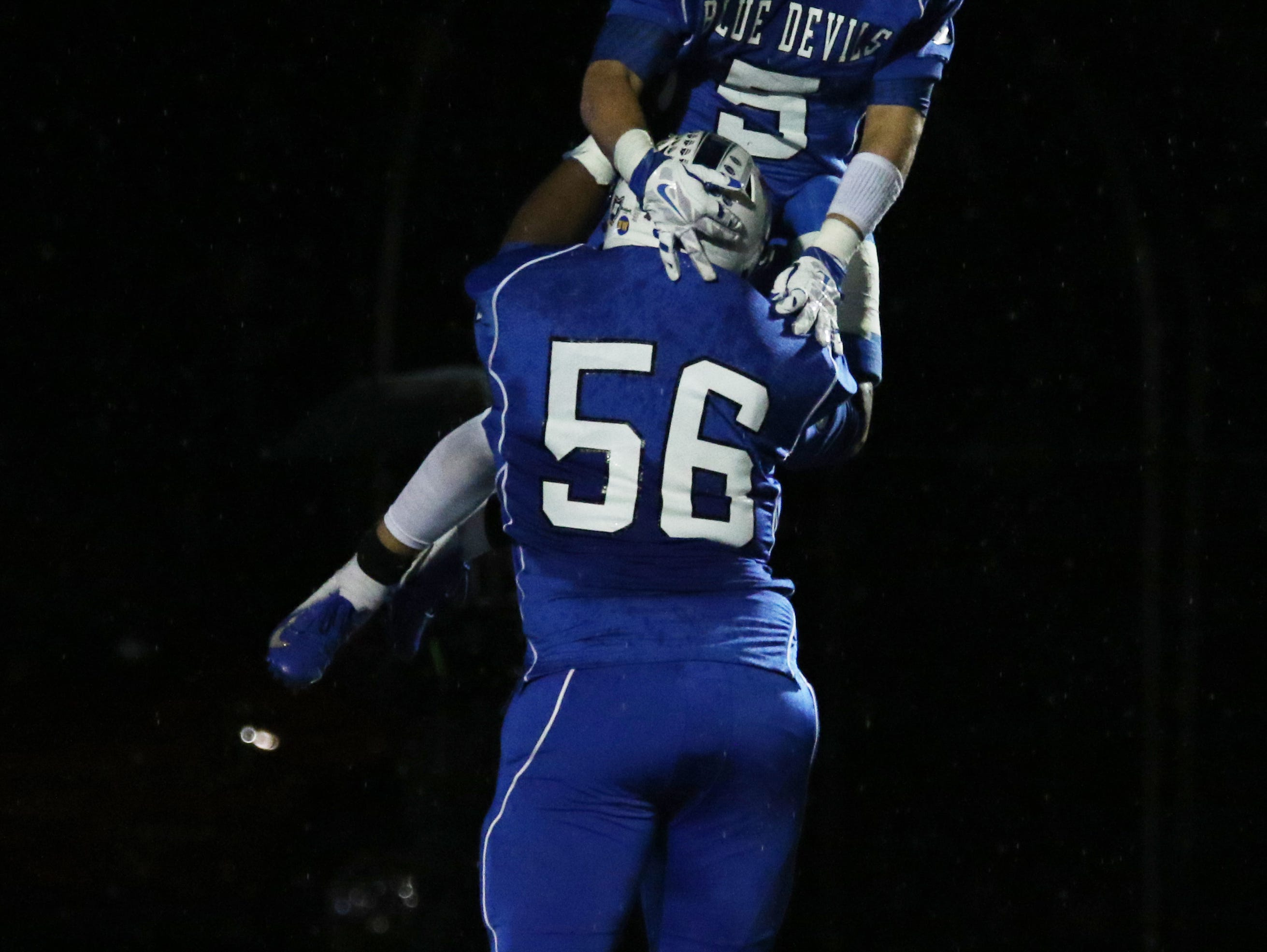Zanesville's Jeremiah Hollins gives teammate JC Curtis a lift after Curtis' touchdown against New Philadelphia.