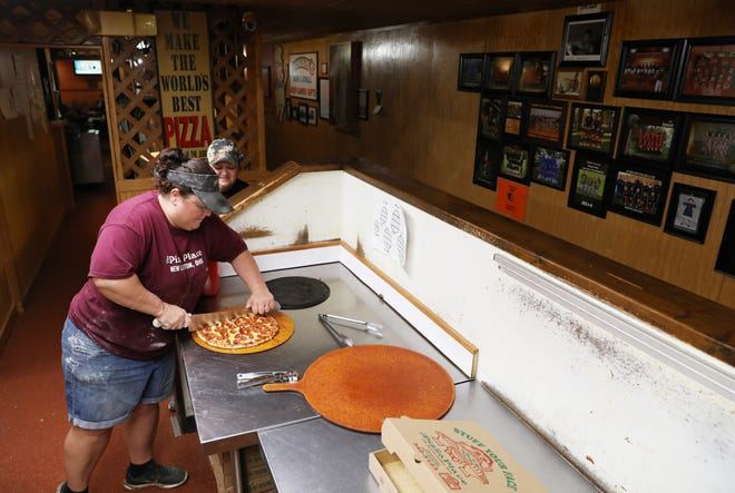 Lori Shipley cuts a pizza at The Pizza Place in New Lexington. The restaurant, located on East Broadway, has been owned and operated by Vic and Mary Ruth Paini since 1983.