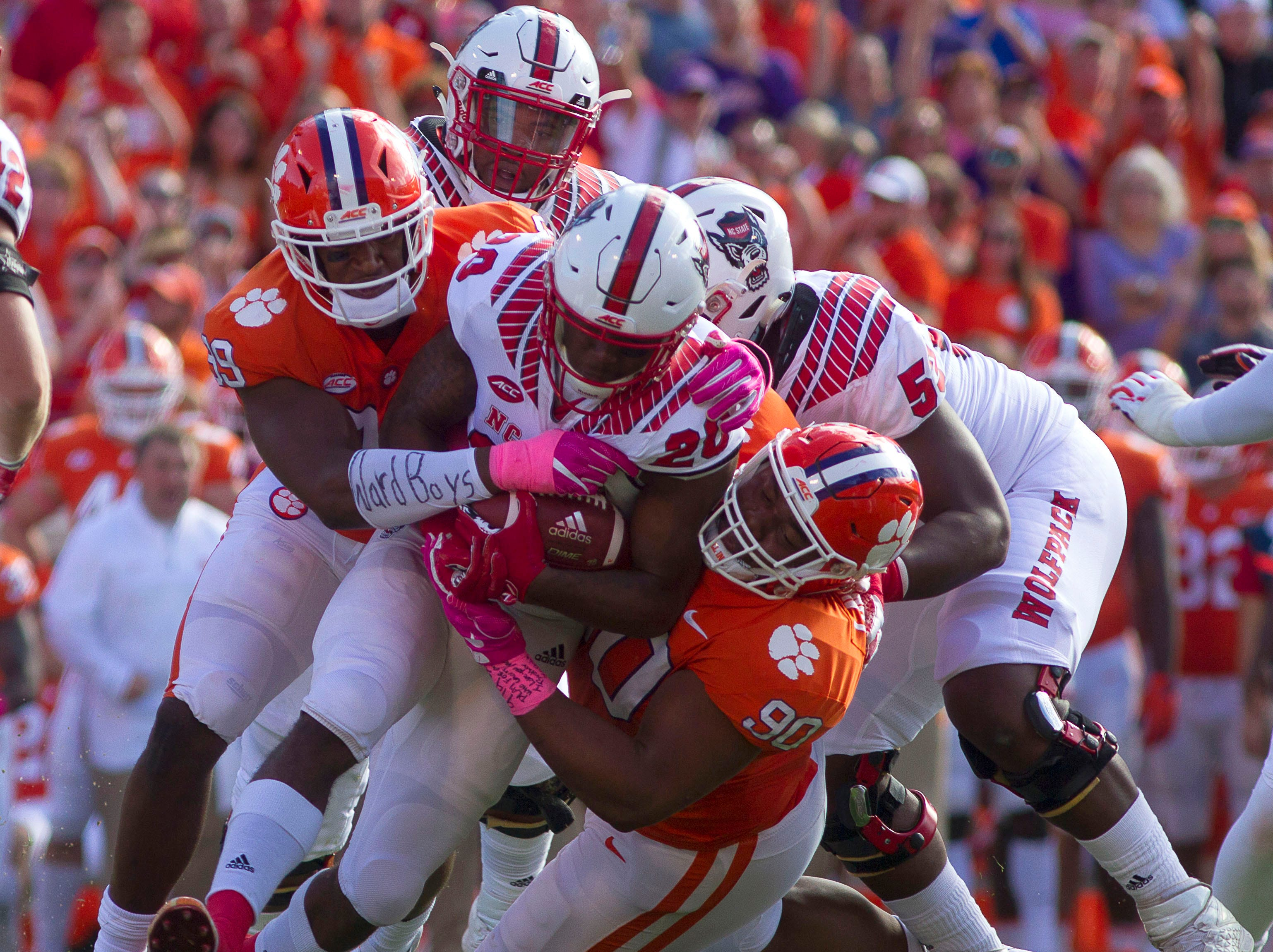 North Carolina State Wolfpack running back Ricky Person Jr. (20) is brought down by Clemson Tigers defensive tackle Dexter Lawrence (90) and defensive end Clelin Ferrell (99) during the second quarter of the game at Clemson Memorial Stadium.