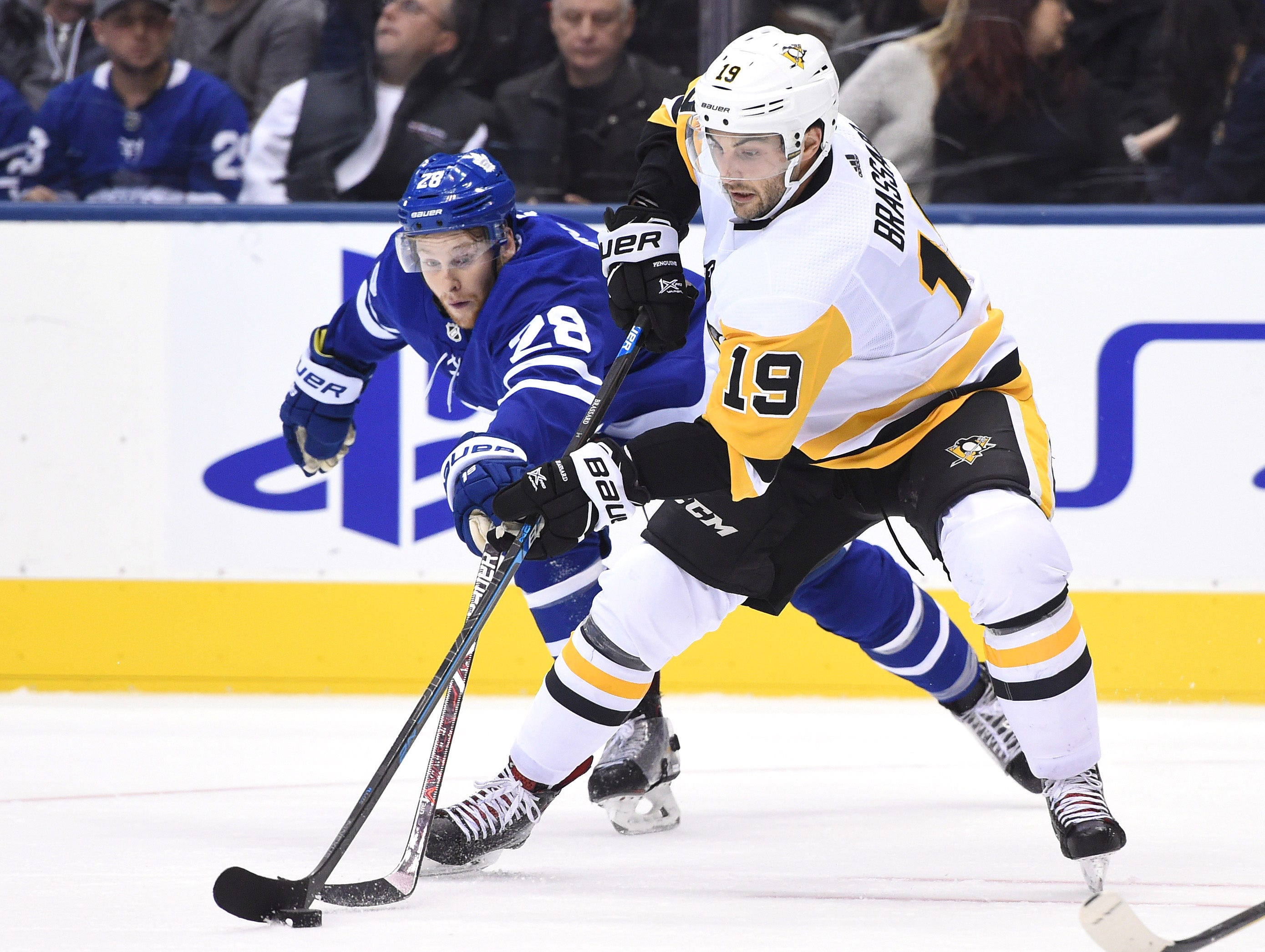 Oct. 18: Toronto Maple Leafs forward Connor Brown (28) attempts to poke the puck away from Pittsburgh Penguins forward Derick Brassard (19) in the third period at Scotiabank Arena.