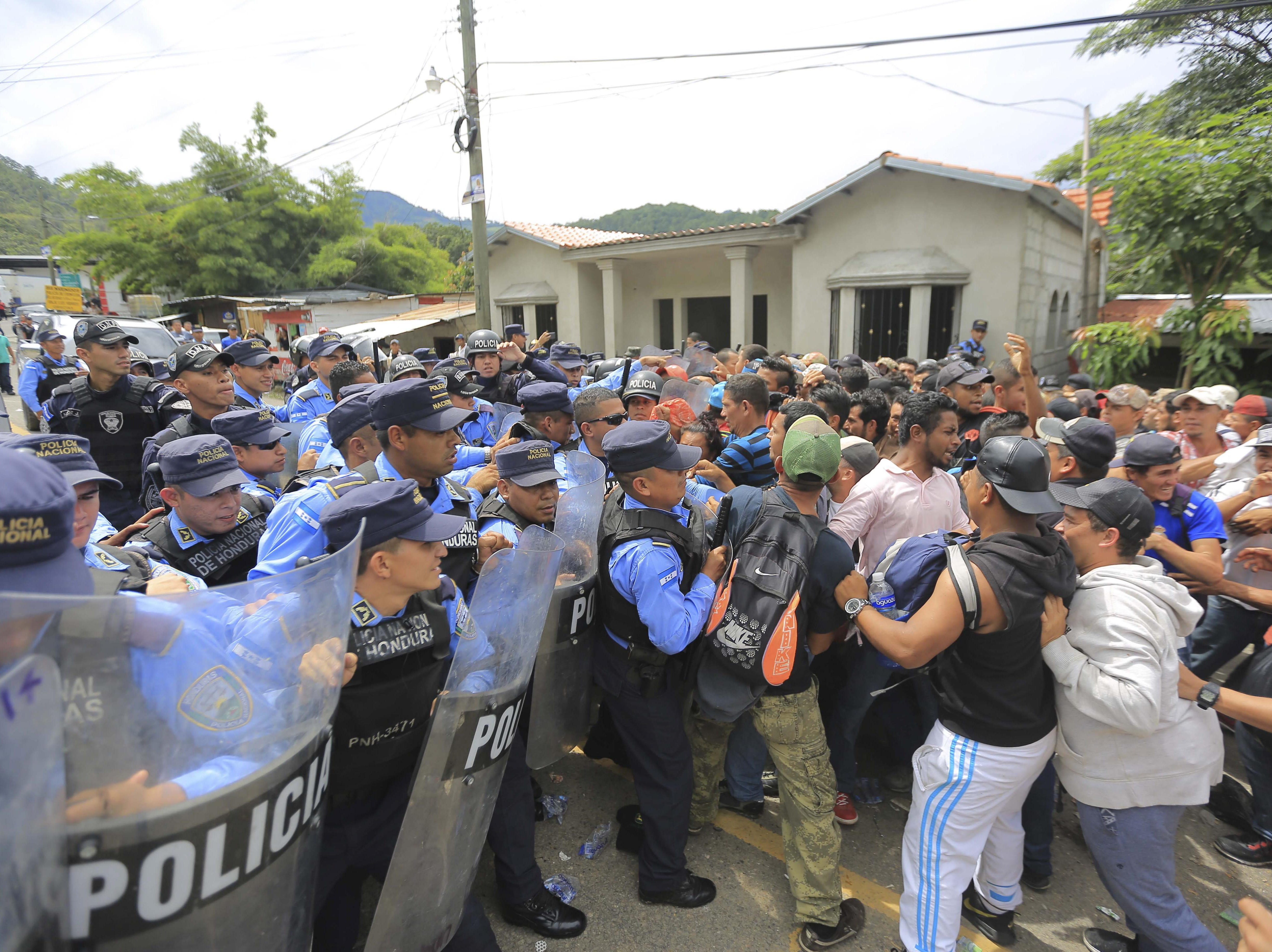Police try to prevent hundreds of Honduran migrants to cross a police checkpoint to Guatemala, at the Agua Caliente border crossing, in Ocotepeque, Honduras on Oct. 19, 2018.