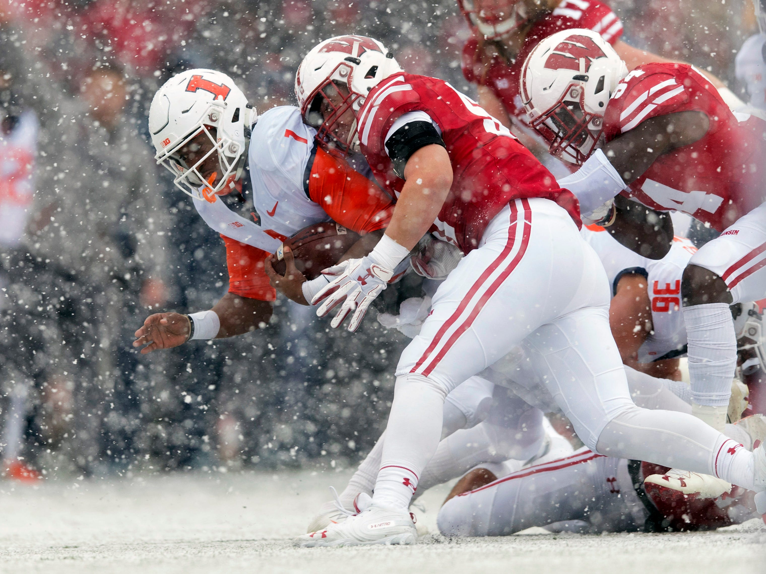 Wisconson defenders wrap up Illinois quarterback AJ Bush Jr. during the first half as the snow flies.
