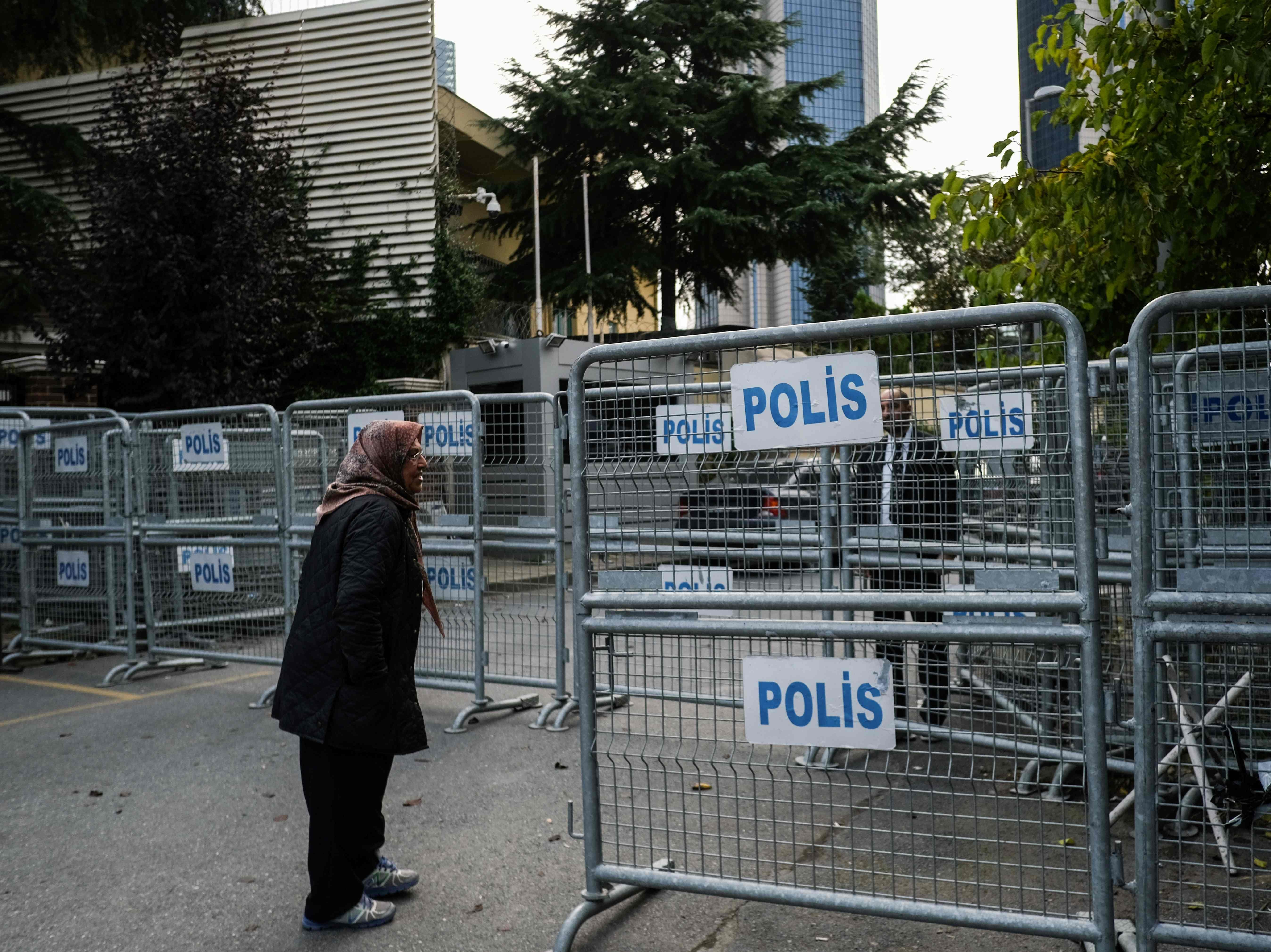 """A woman stands next to police barriers, in front of the Saudi consulate in Istanbul, on Oct. 20, 2018. Saudi Arabia admitted on October 20, 2018 that critic Jamal Khashoggi was killed inside its Istanbul consulate, saying he died during a """"brawl"""", as Turkey vowed to release the full findings of its own investigation."""
