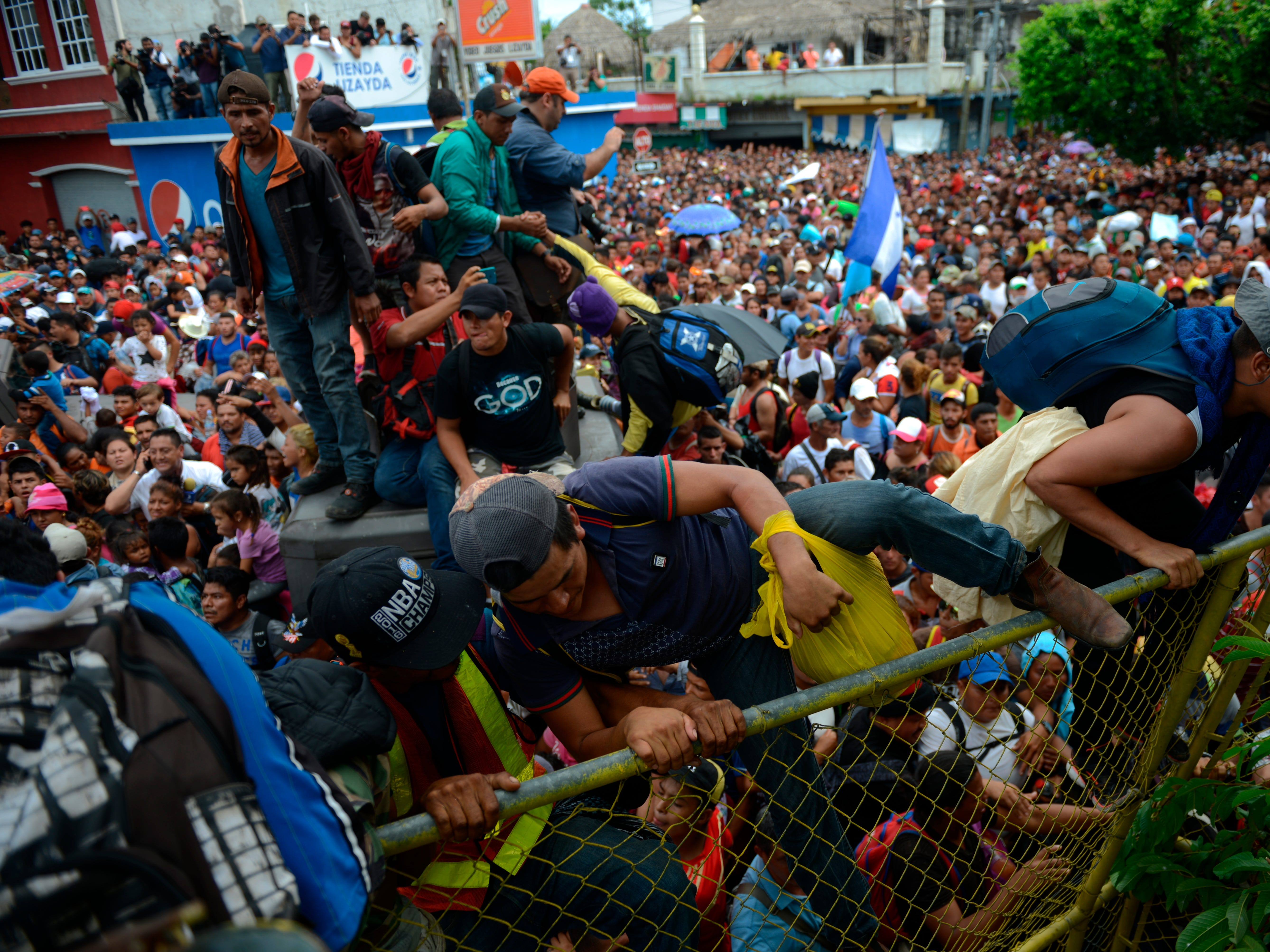 Honduran migrants climb a border fence, in Tecun Uman, Guatemala, Friday, Oct. 19, 2018. Migrants broke down the gates at the border crossing and began streaming toward a bridge into Mexico. After arriving at the tall, yellow metal fence some clambered atop it and on U.S.-donated military jeeps. Young men began violently tugging on the barrier and finally succeeded in tearing it down.