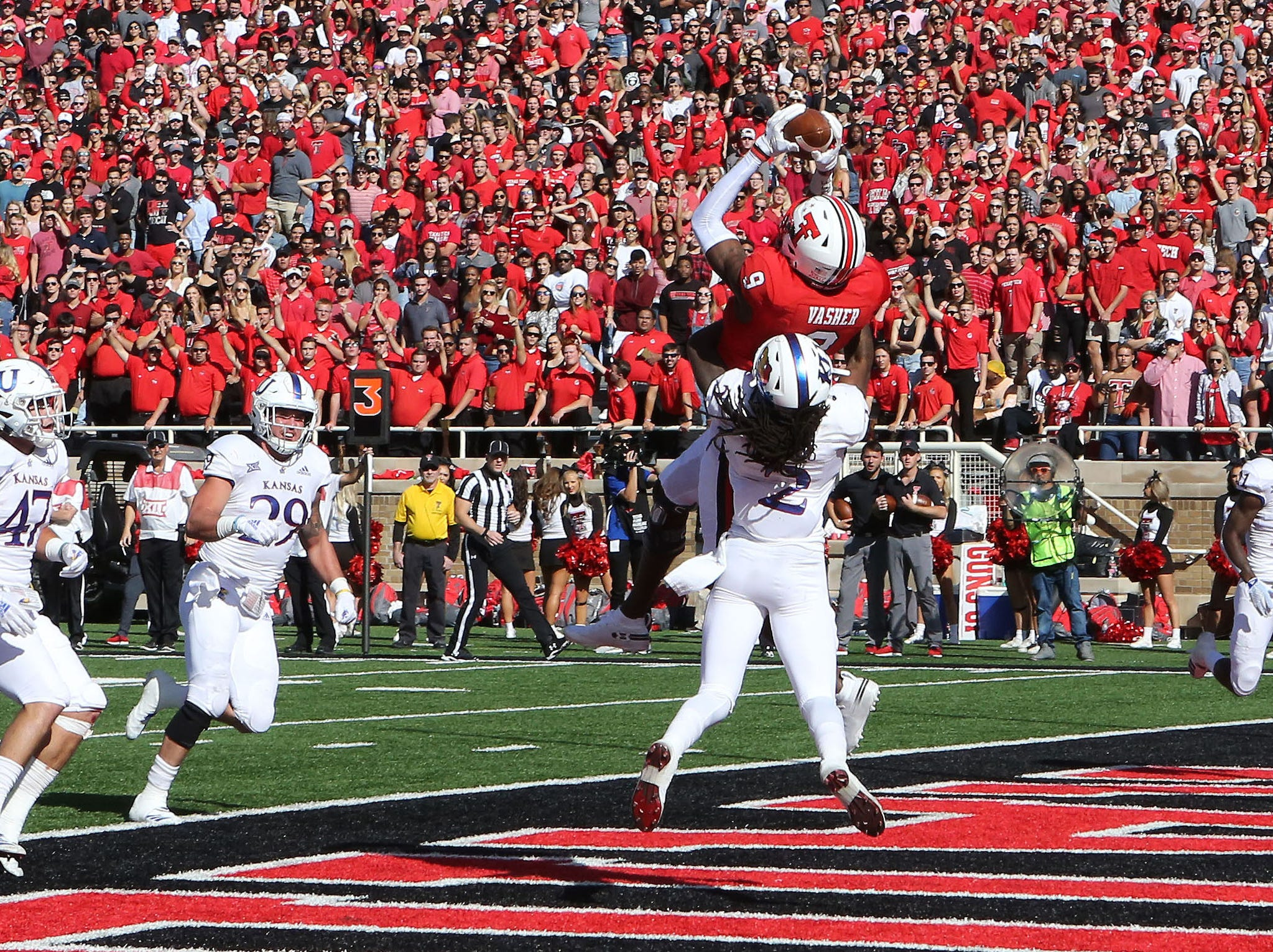 Texas Tech Red Raiders wide receiver TJ Vasher (9) catches a touchdown pass against Kansas Jayhawks defensive corner back Corione Harris (2) in the first half at Jones AT&T Stadium.