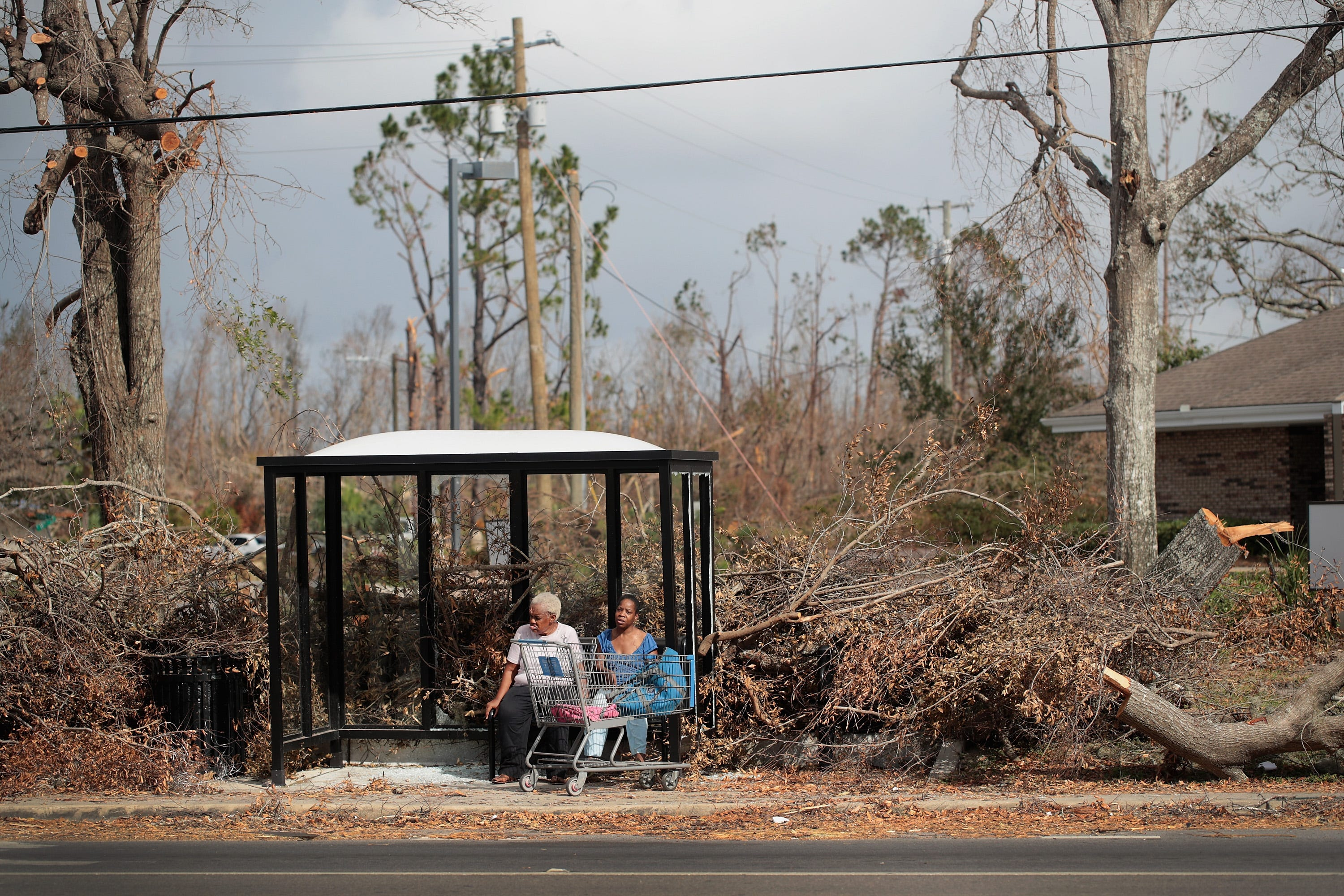 Mary Battles, left, and Shenike Bishop rest in a bus stop damaged by Hurricane Michael on Oct. 20, 2018 in Panama City, Florida. Hurricane Michael slammed into the Florida Panhandle on October 10, as a category 4 storm causing massive damage and claiming about 30 lives.