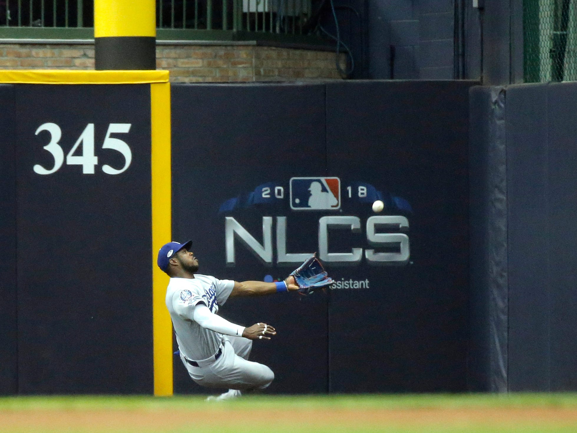 NLCS Game 6: Dodgers right fielder Yasiel Puig can't make a catch on a ball hit by Jesus Aguilar in the seventh inning.