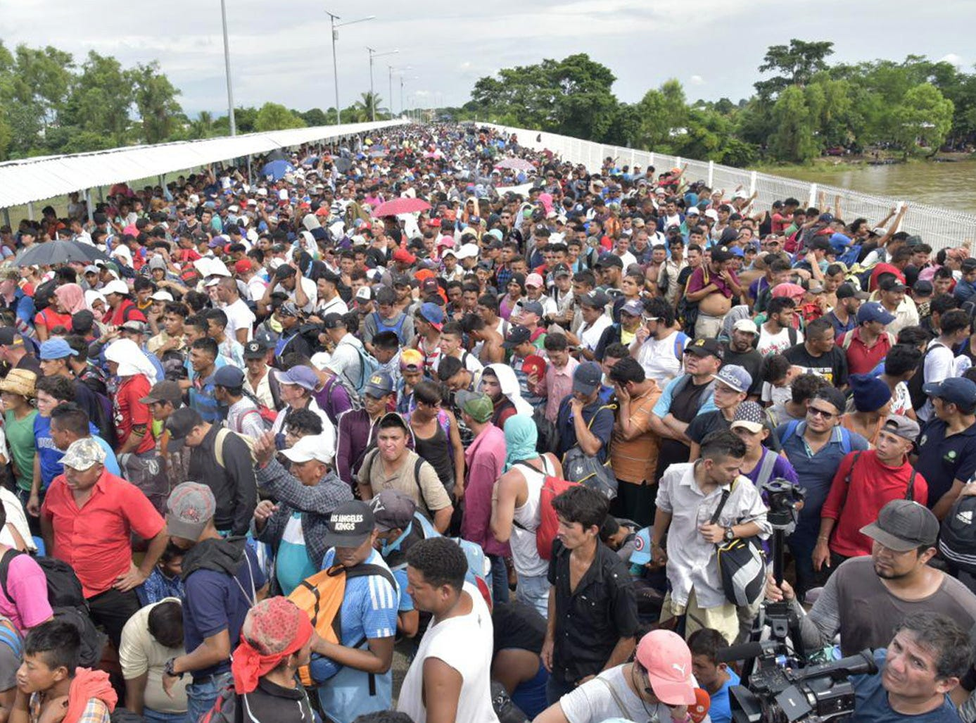 Thousands of Honduran migrants wait for access on the bridge that crosses the Suchiate River after crossing the fence on the border with Guatemala to enter in Ciudad Hidalgo, Mexico on Oct. 19, 2018.