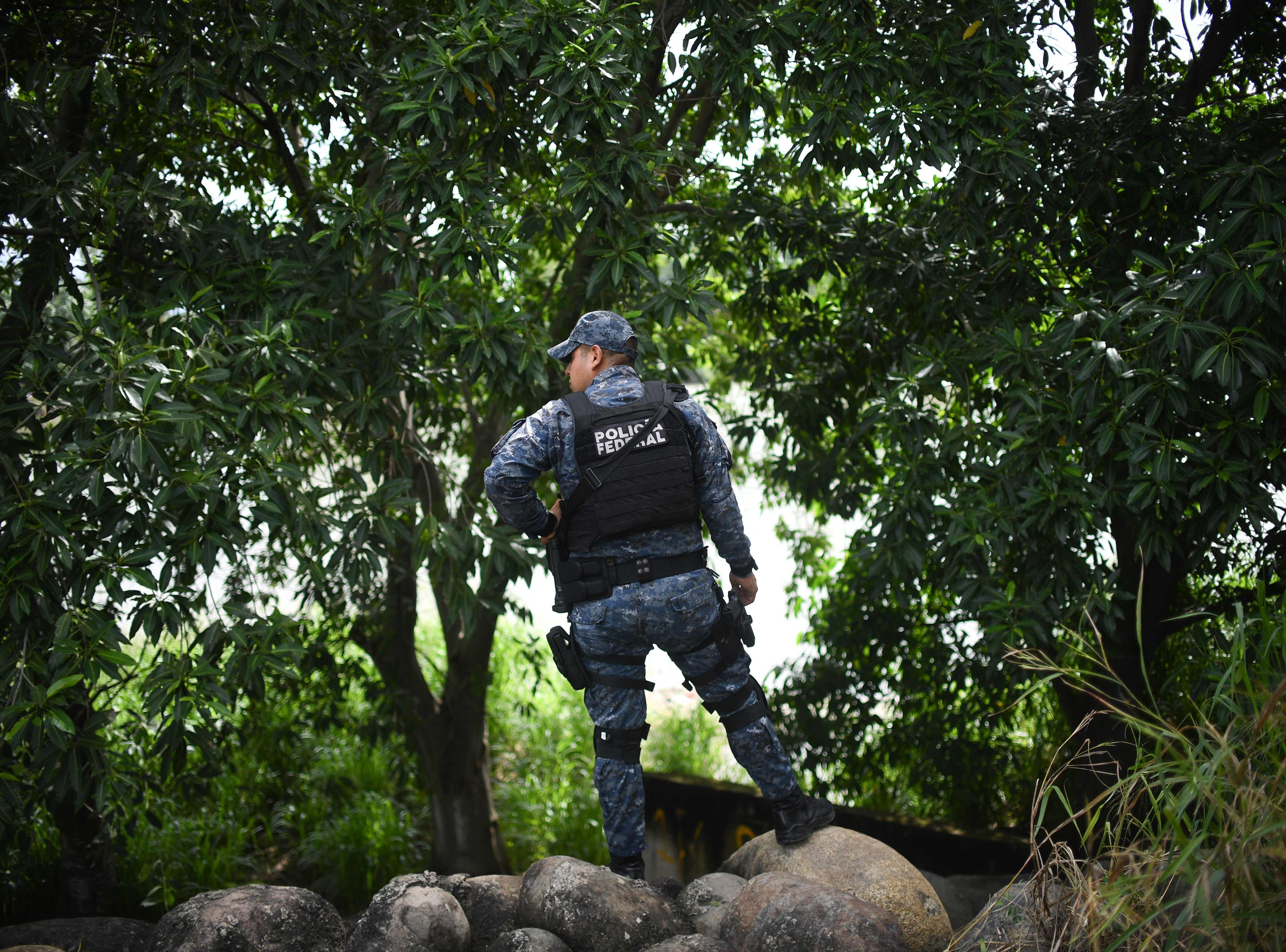 A Mexican Federal Police officer stands guard on the bank of the Suchiate River in Ciudad Hidalgo, Chiapas state, Mexico, while a caravan of Honduran migrants heading to the US tries to get to Mexican territory from Guatemala, on Oct. 20, 2018.