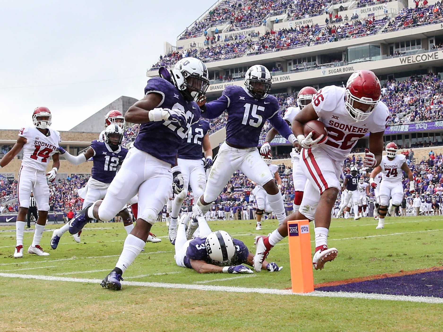 Oklahoma Sooners running back Kennedy Brooks (26) races past TCU Horned Frogs defenders for a first-half touchdown.