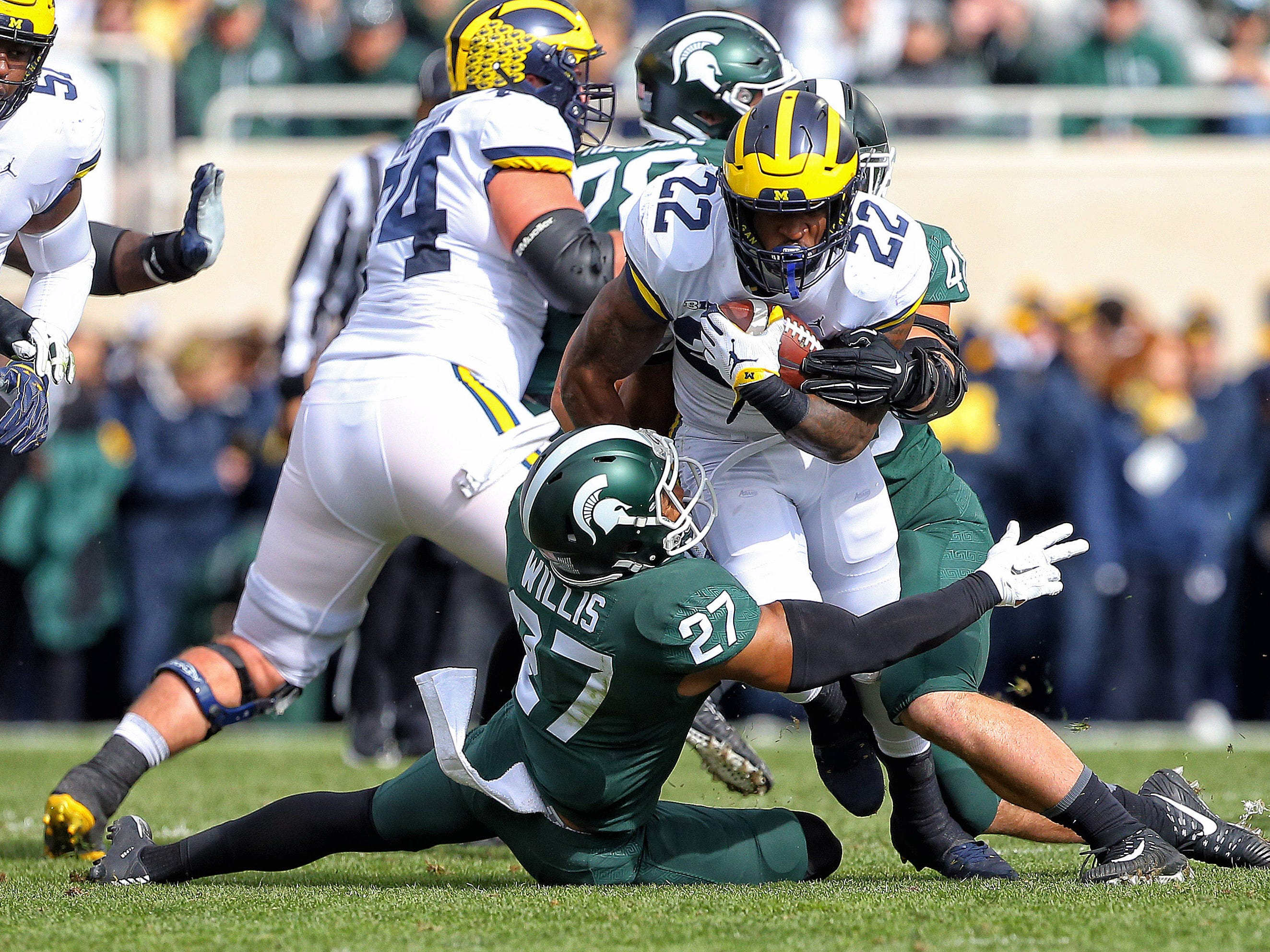 Michigan Wolverines running back Karan Higdon (22) runs though the tackle of Michigan State Spartans safety Khari Willis (27) during the first quarter at Spartan Stadium.