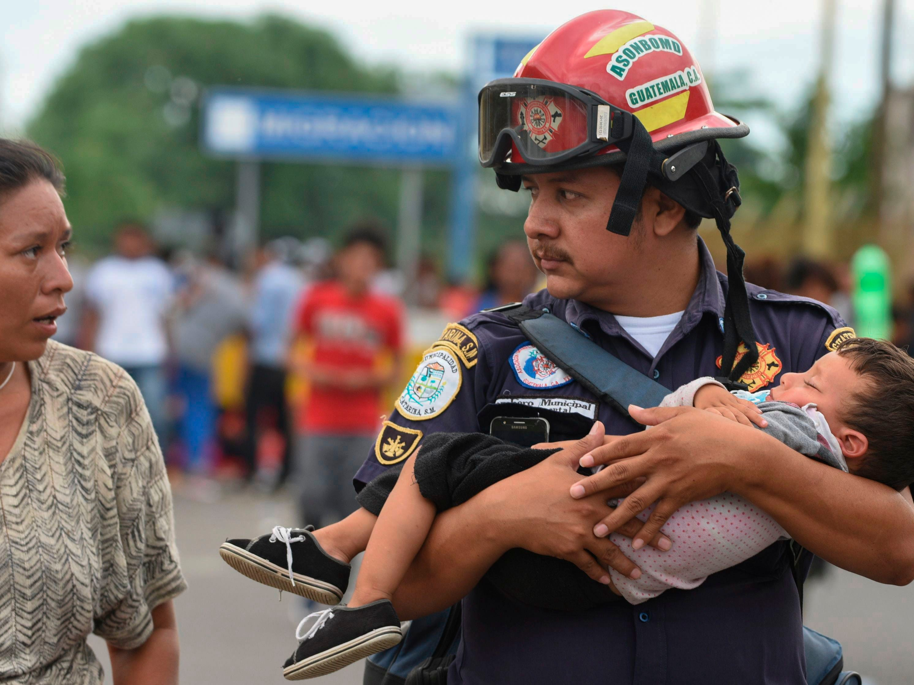 A Guatemalan firefighter carries an ailing baby, as an Honduran migrant caravan heading to the US, reaches the Guatemala-Mexico international bridge in Tecun Uman, Guatemala on Oct. 19, 2018.