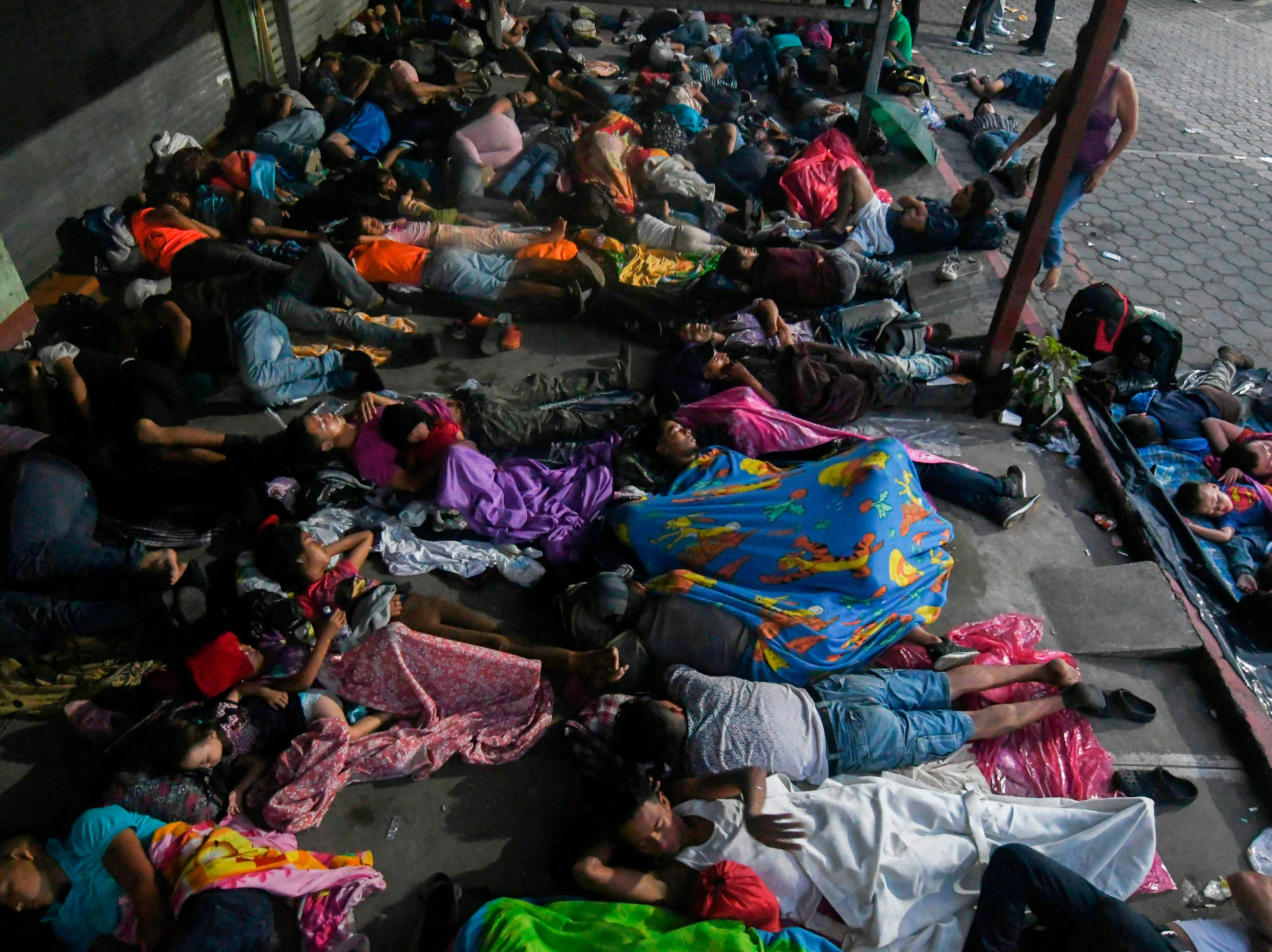 Honduran migrants taking part in a caravan heading to the US, sleep in the main square of Ciudad Tecun Uman, Guatemala, in the border with Mexico, on Oct. 20, 2018. Thousands of migrants who forced their way through Guatemala's northwestern border and flooded onto a bridge leading to Mexico, where riot police battled them back, on Saturday waited at the border in the hope of continuing their journey to the United States.