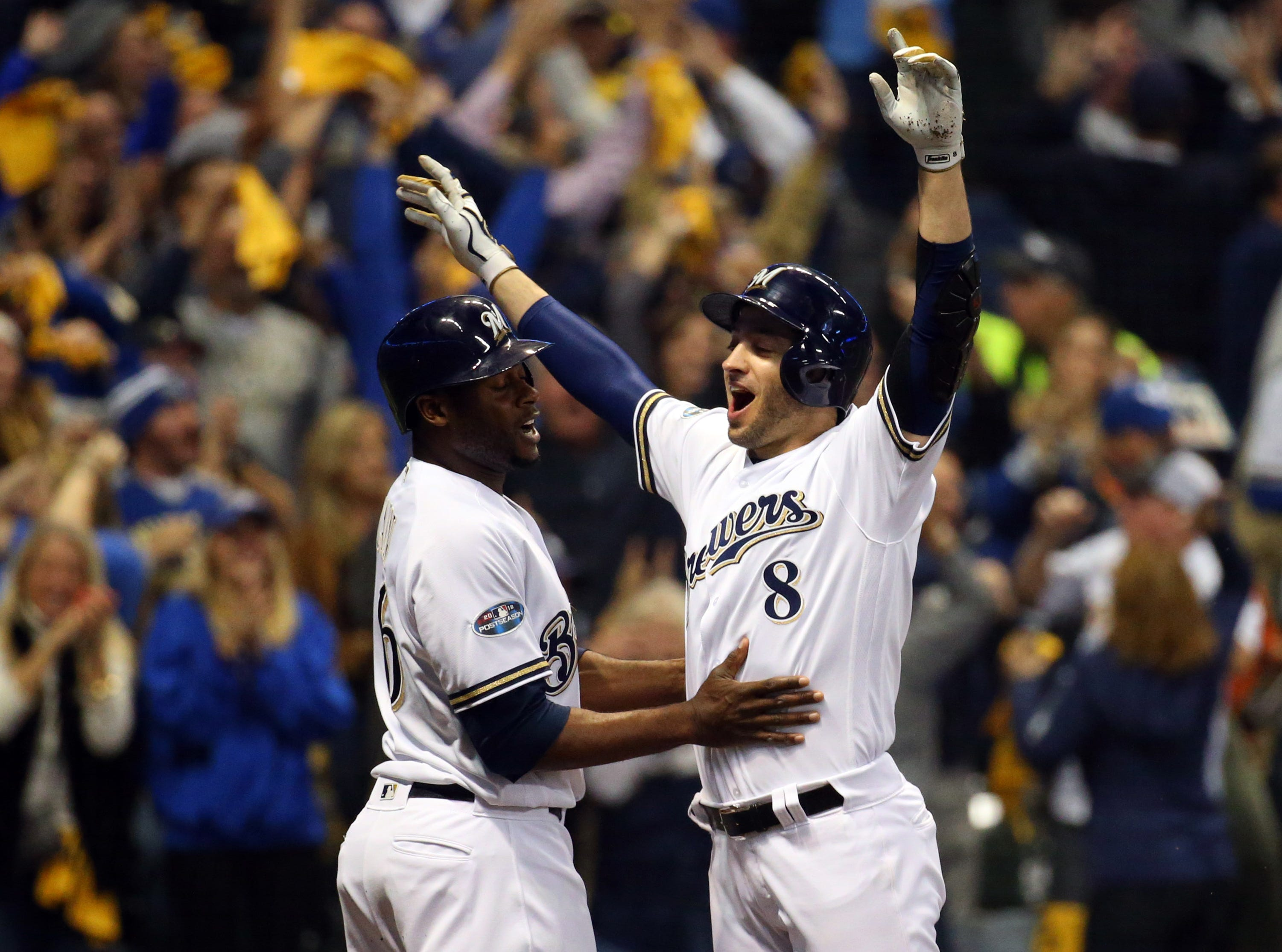 NLCS Game 6: Lorenzo Cain and Ryan Braun celebrate after scoring in the first inning.