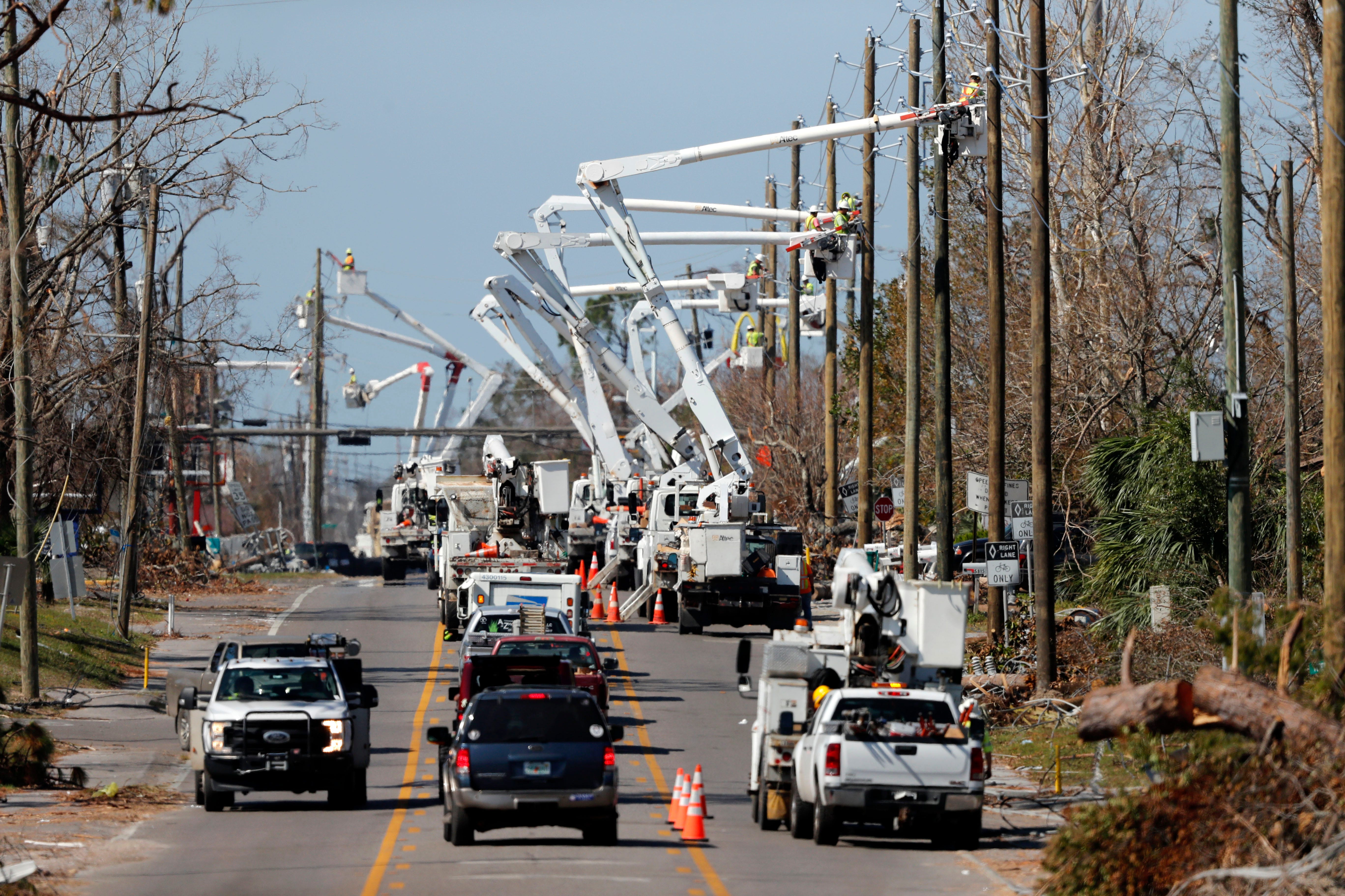 In this Thursday, Oct. 18, 2018 photo, utility crews set up new poles and utility wires in the aftermath of Hurricane Michael in Panama City, Fla.