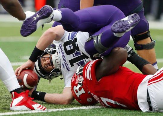 Rutgers Scarlet Knights defensive lineman Elorm Lumor sacks Northwestern Wildcats quarterback Clayton Thorson in the first half.