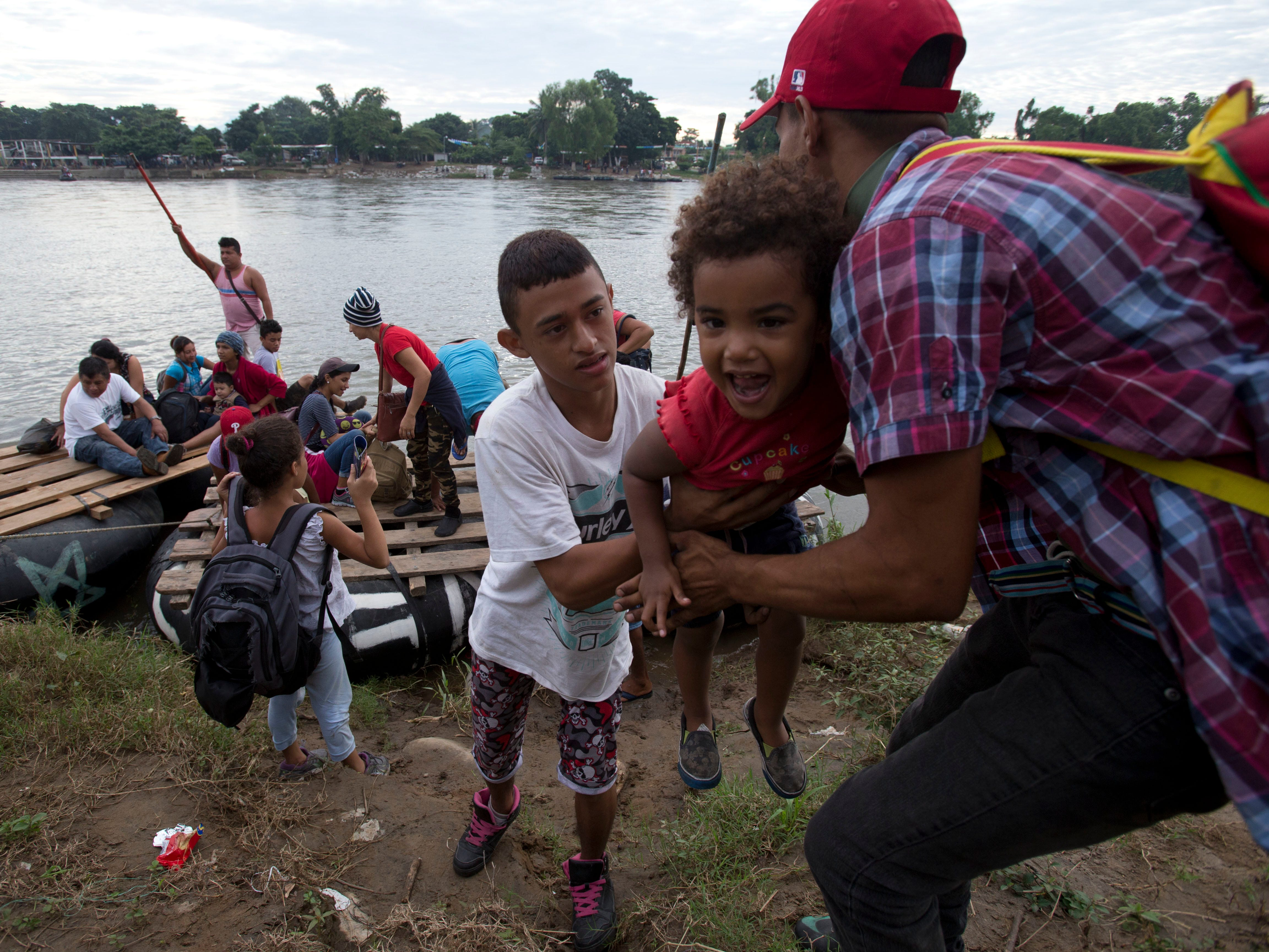A group of Honduran migrants arrives to the Mexican side of the border after crossing the Suchiate River aboard a raft made out of tractor inner tubes and wooden planks, on the the border with Guatemala, in Ciudad Hidalgo, Mexico, Saturday, Oct. 20, 2018. The entry into Mexico via the bridge that connects the two countries has been closed. The main group of migrants have moved about 30 feet back from the gate that separates them from Mexican police to establish a buffer zone. About 1,000 migrants now remain on the bridge between Guatemala and Mexico.