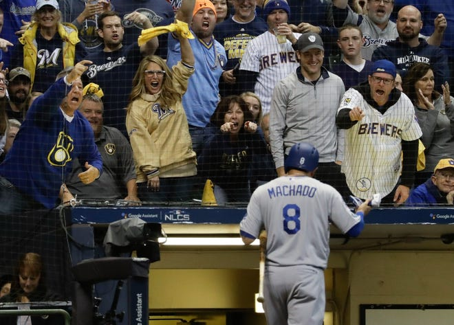 Brewers fans give Dodger Manny Machado a warm welcome back to the dugout after he struck out in his first at-bat in his return to Miller Park.