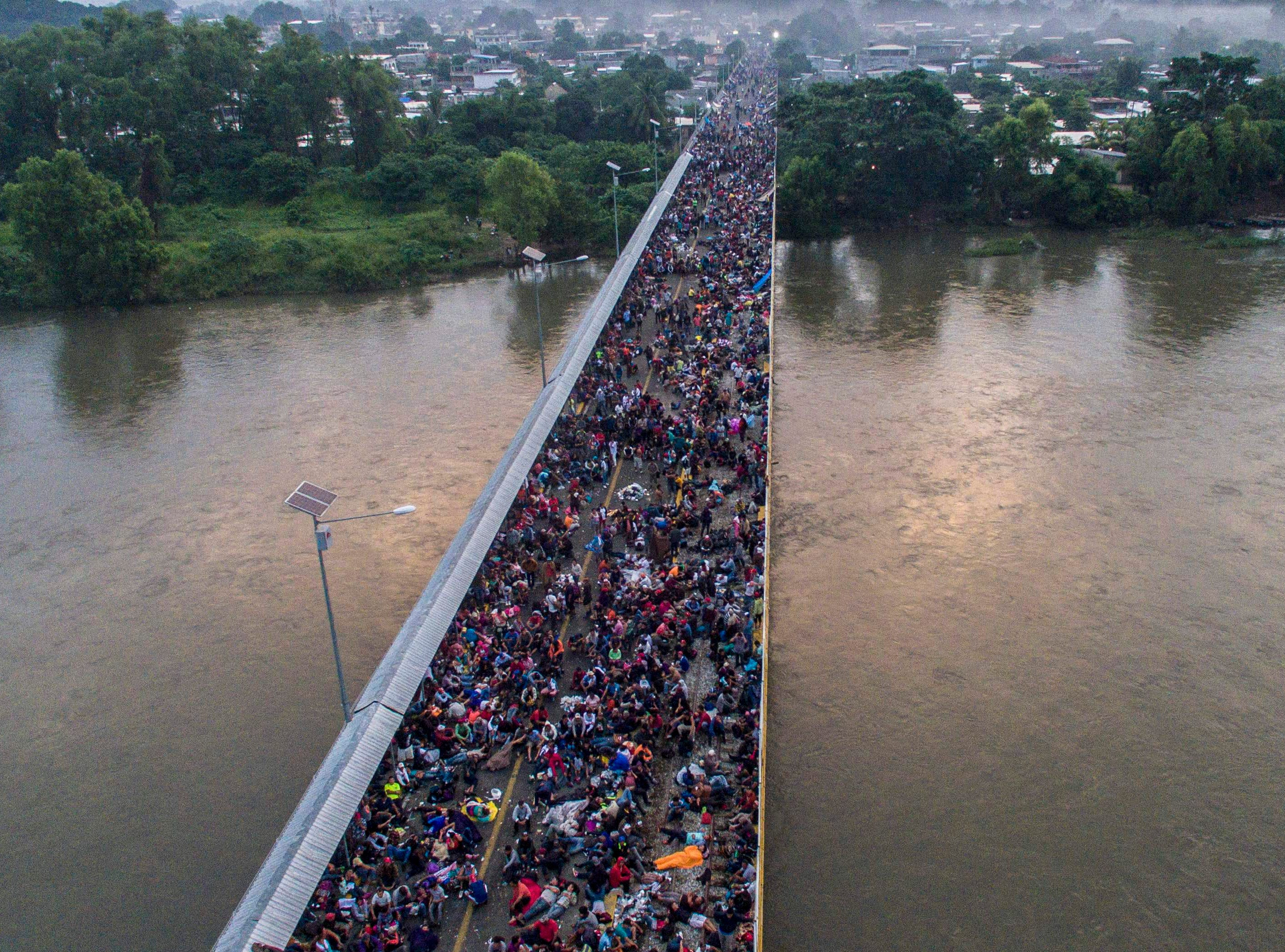 Aerial view of a Honduran migrant caravan heading to the US, on the Guatemala-Mexico international border bridge in Ciudad Hidalgo, Chiapas state, Mexico, on Oct. 20, 2018.