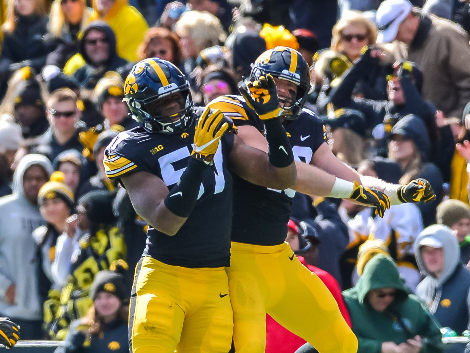 Iowa Hawkeyes defensive end Chauncey Golston (57) and defensive end Parker Hesse (40) celebrate during the fourth quarter against the Maryland Terrapins at Kinnick Stadium.