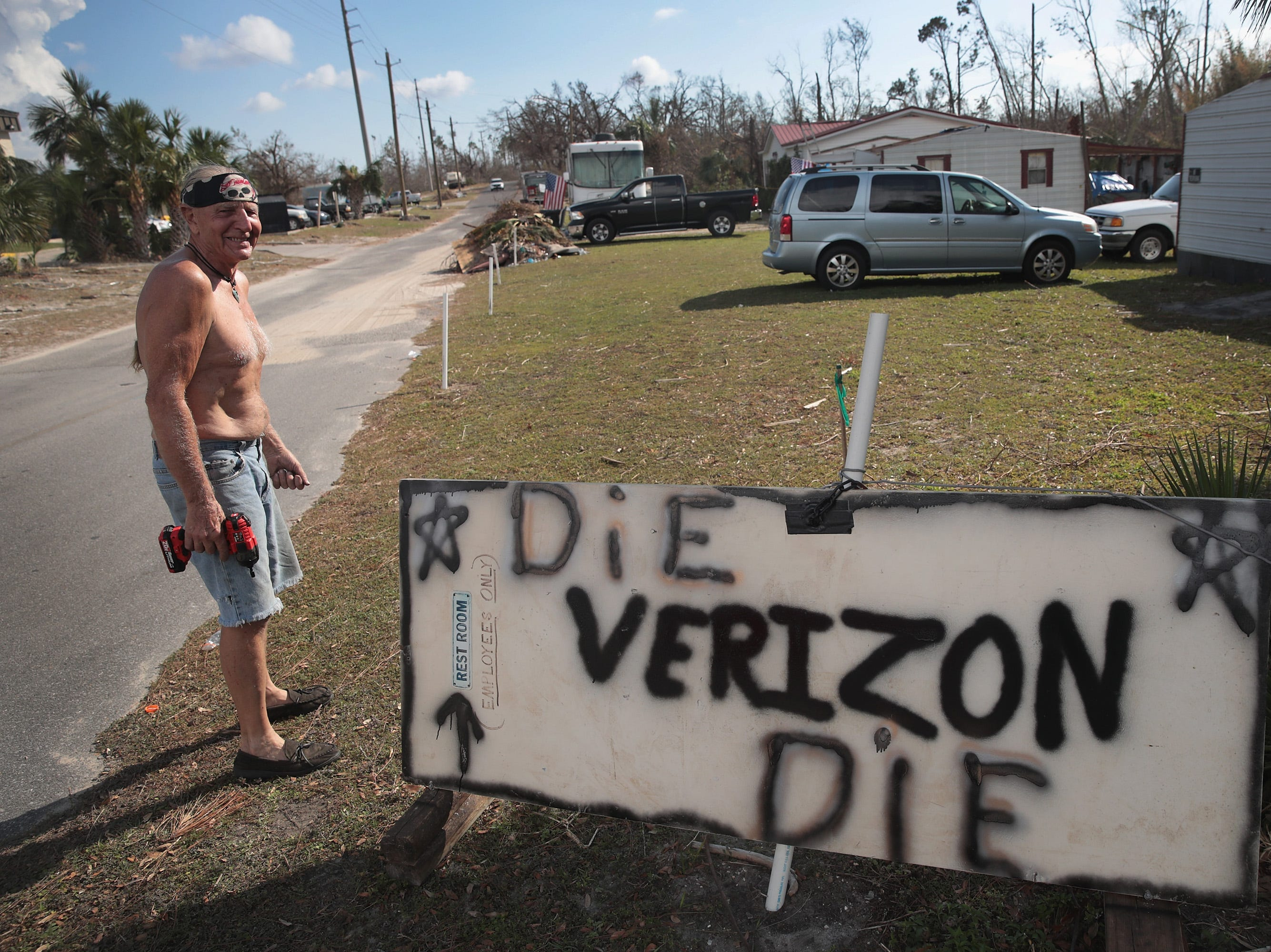 Mark Mauldin hangs a sign near the front of his property expressing his dissatisfaction with his Verizon cell phone service following Hurricane Michael on Oct. 19, 2018 in Panama City, Fla.