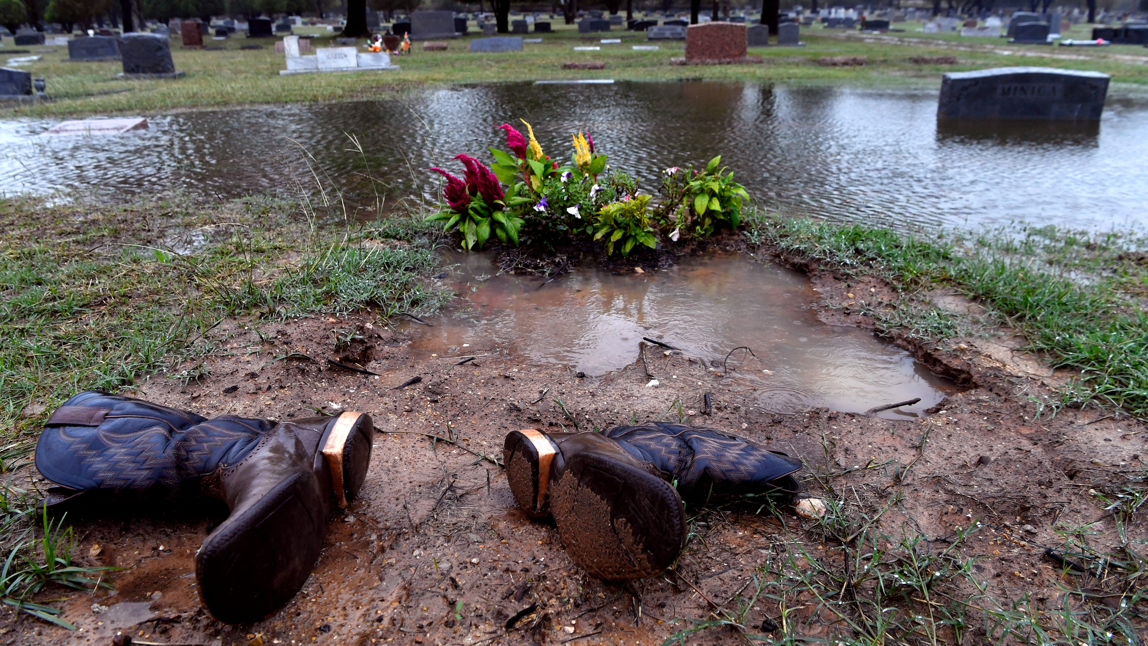 Boots are laid beside a grave as rains fall Wednesday Oct. 17, 2018 at Brownwood's Greenleaf Cemetery. The resting place of author Robert E. Howard, the cemetery turned 150 years-old this year.