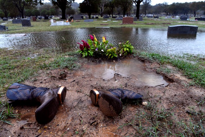 Boots are laid beside a grave as rains fall Wednesday at Brownwood's Greenleaf Cemetery. The resting place of author Robert E. Howard, the cemetery turned 150 years old this year.