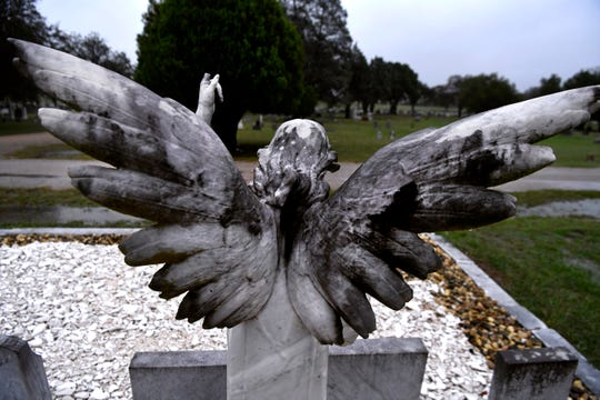 The wings of a statuary angel spread over the plot for the Smith family at Greenleaf Cemetery.