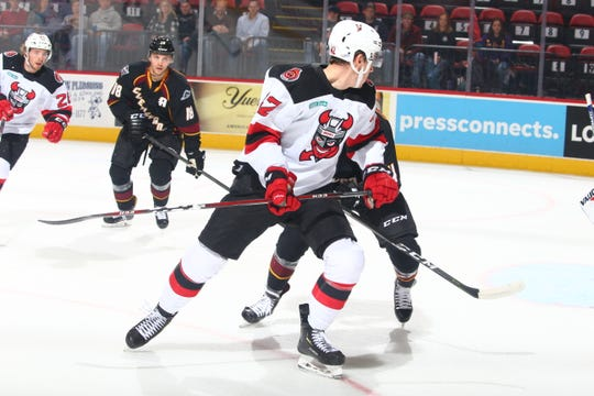 The Binghamton Devils' john Quenneville battles for position Saturday night at the Floyd L. Maines Veterans Memorial Arena.