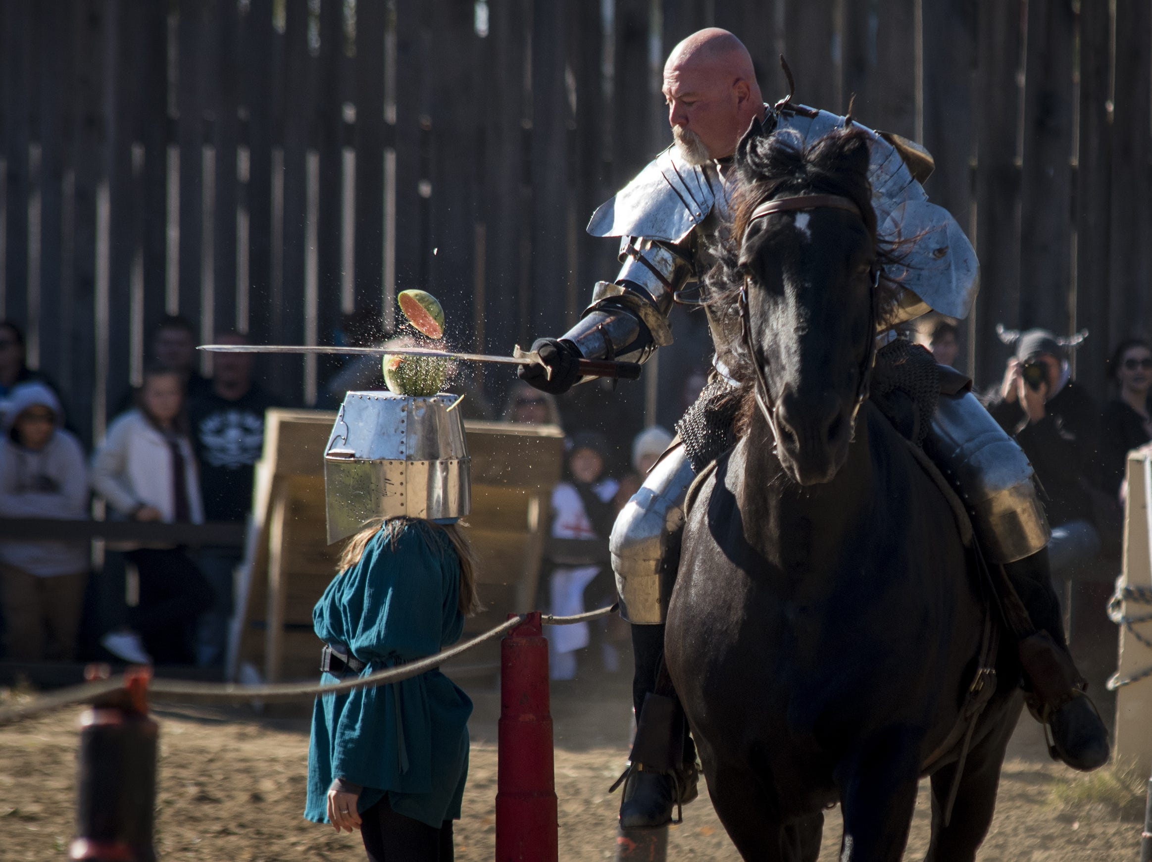 Sir Robert chops a watermelon in half as it is balanced on someone's head during the live jousting show at the Ohio Renaissance Festival Sunday, October 21, 2018 in Waynesville, Ohio.