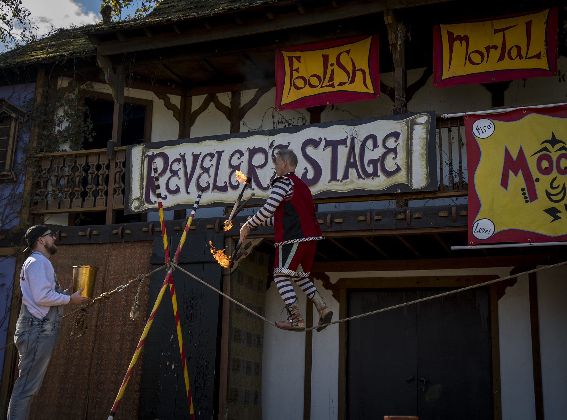 Stage performer Moonie juggles fire sticks on a tightrope at the Ohio Renaissance Festival Sunday, October 21, 2018 in Waynesville, Ohio.