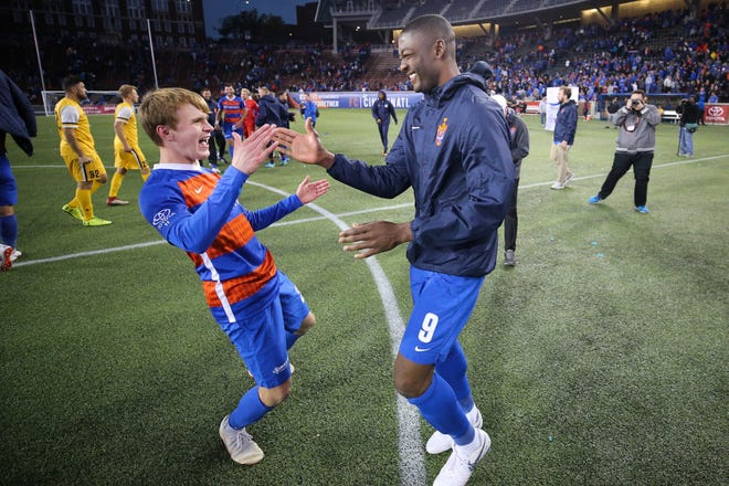 FC Cincinnati midfielder Jimmy McLaughlin (20), left, and FC Cincinnati Fanendo Adi (9), right, high five after the 6-5 penalty win during a USL soccer playoff game between Nashville SC and FC Cincinnati,Saturday, Oct. 20, 2018, at Nippert Stadium in Cincinnati. FC Cincinnati won 6-5 on penalties.