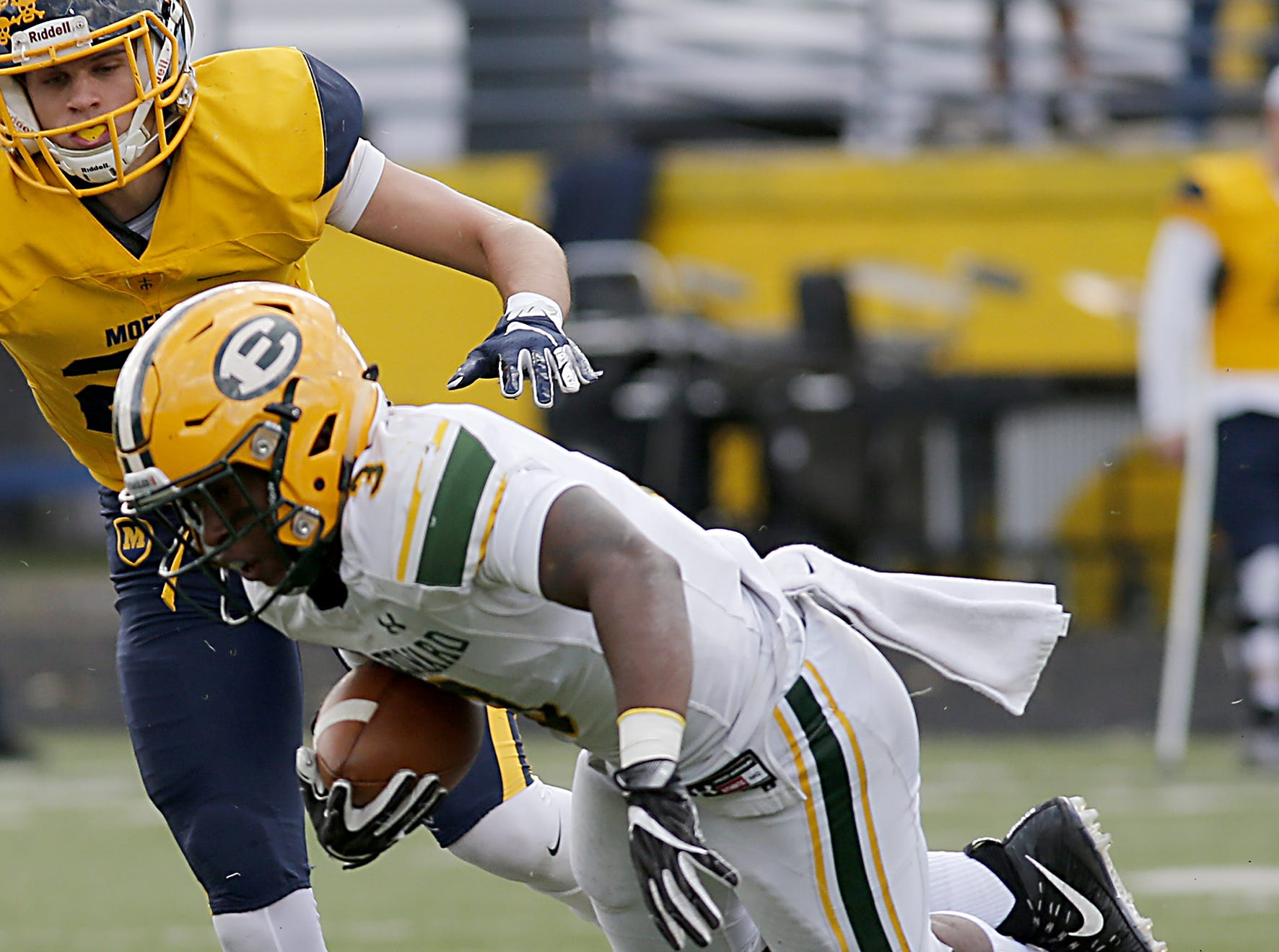 Lakewood St. Edward running back Jordan Castleberry is tripped up by Moeller defensive back Carrington Valentine during their game at Lockland Saturday, Oct. 20, 2018.