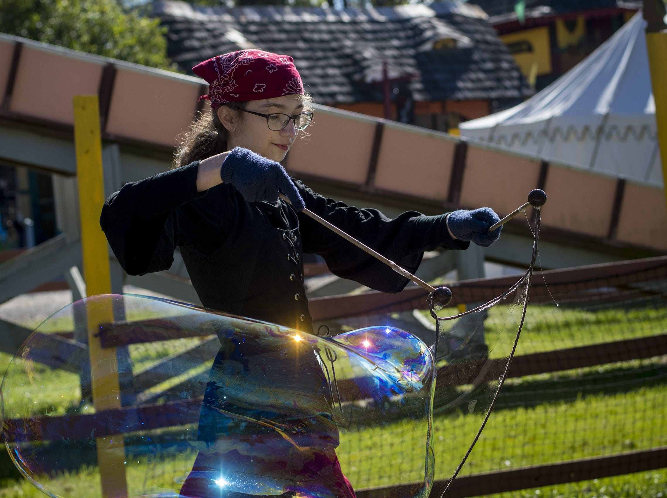 Isabel Voyd of Greenfield make giant bubbles during Romance Weekend at the Ohio Renaissance Festival Sunday, October 21, 2018 in Waynesville, Ohio.