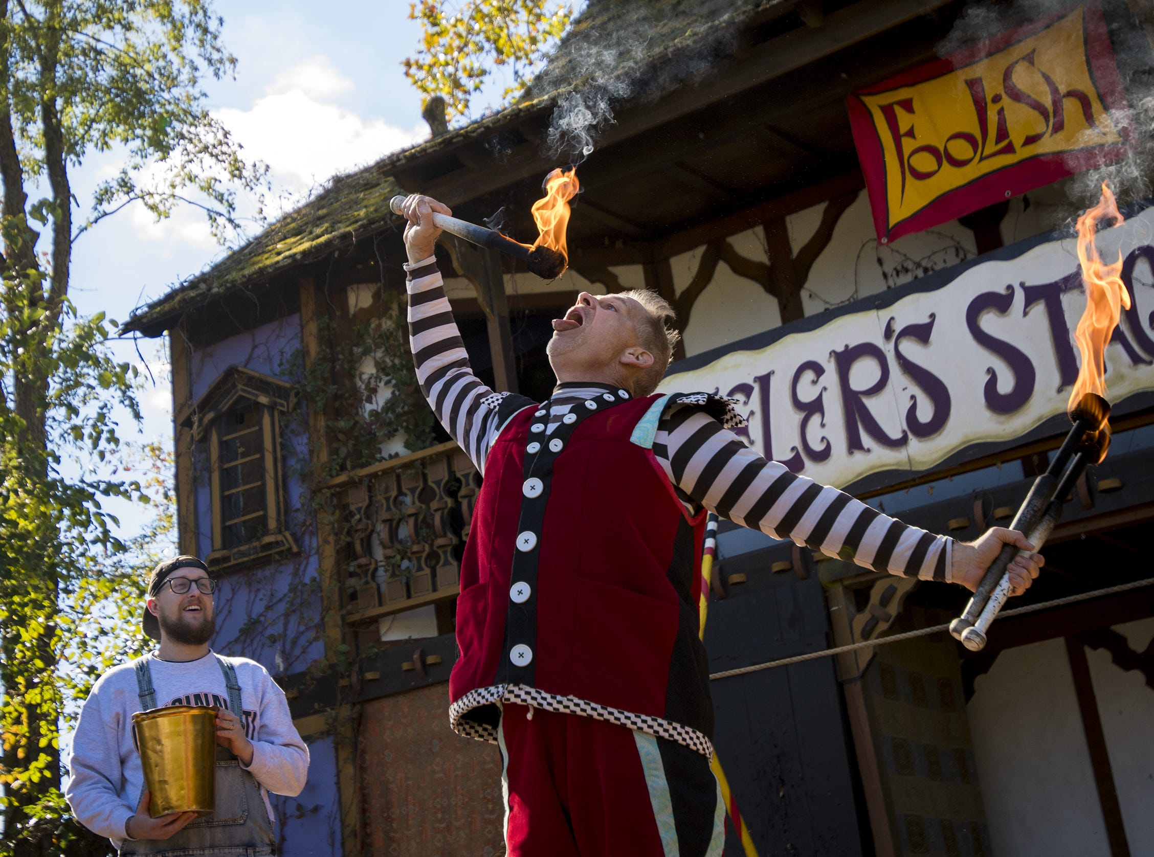 Stage performer Moonie tries to blow out his fire sticks during the Ohio Renaissance Festival Sunday, October 21, 2018 in Waynesville, Ohio.
