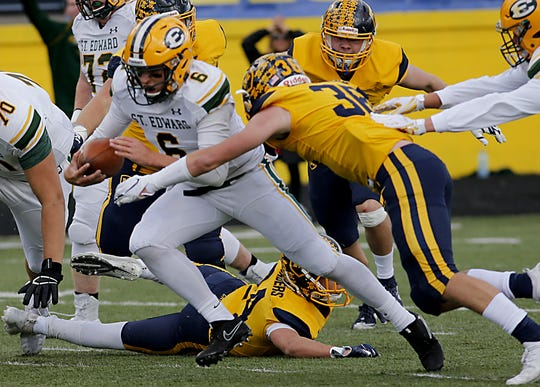 Lakewood St. Edward quarterback Garrett Dzuro is wrapped up by Moeller defensive back Zach French during their game at Lockland Saturday, Oct. 20, 2018.