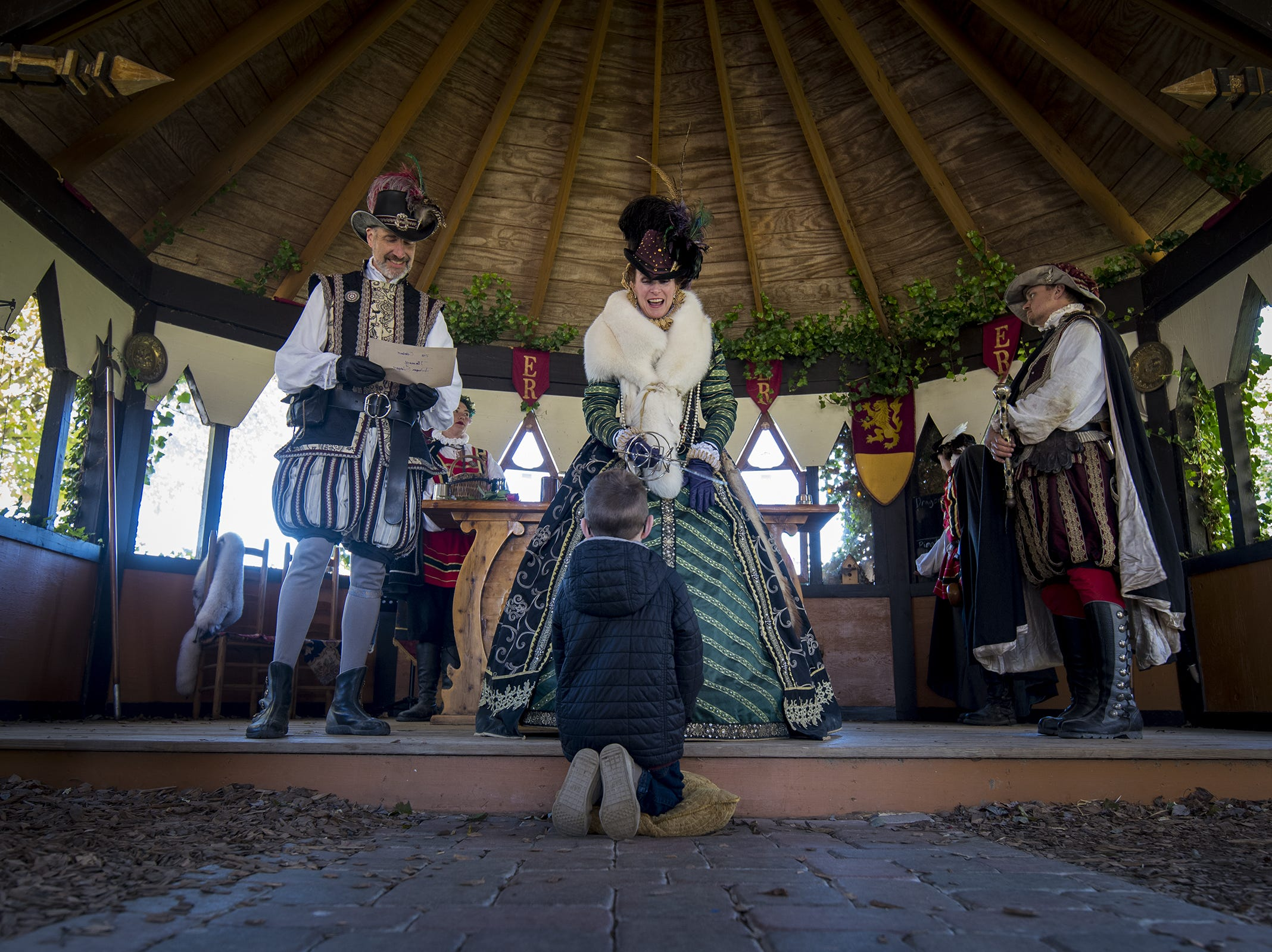 Timmy Manning, 7, of Anderson is knighted during Romance Weekend at the Ohio Renaissance Festival Sunday, October 21, 2018 in Waynesville, Ohio.
