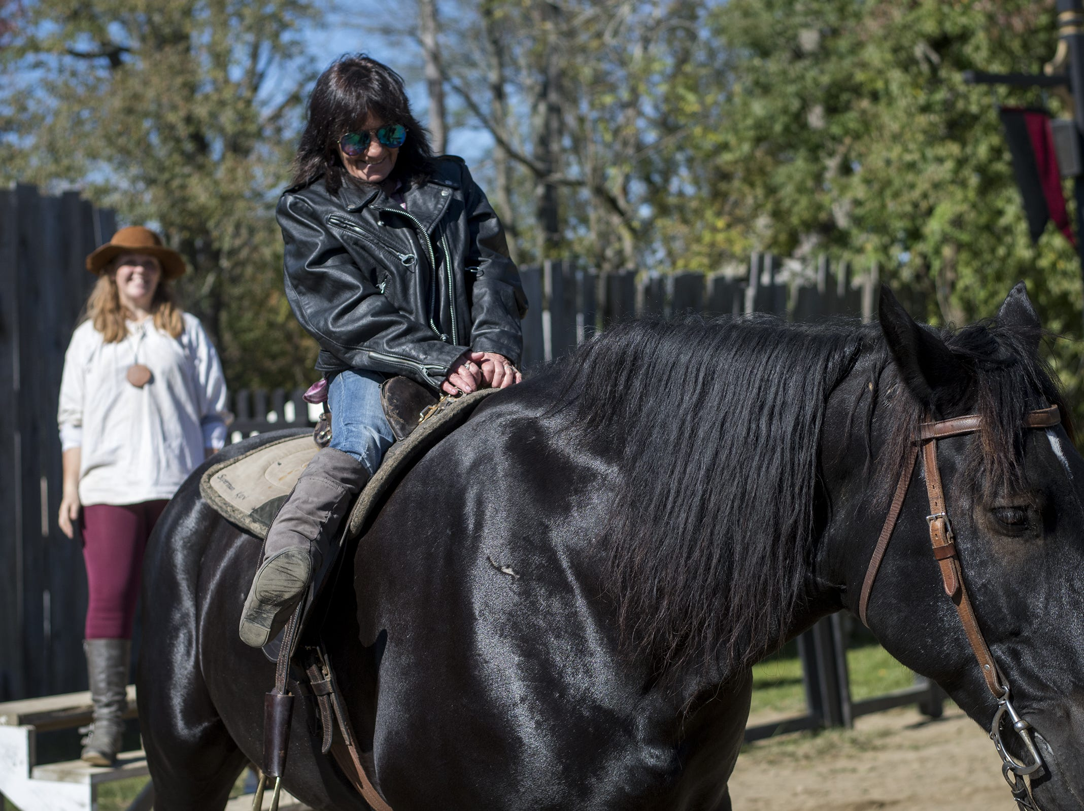 A festival-goer rides one of the knight's horses during Romance Weekend at the Ohio Renaissance Festival Sunday, October 21, 2018 in Waynesville, Ohio.