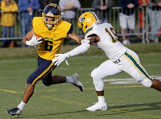 Moeller wide receiver R.J. Khayo tries to avoid Lakewood St. Edward defensive back Lawson Nash during their game at Lockland Saturday, Oct. 20, 2018.