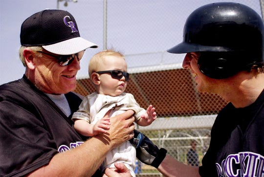 Colorado Rockies infielder Mike Bell, right, hands his son, Luke, to his grandfather and Rockies manager Buddy Bell at Spring Training in Tucson, Ariz., on Thursday, Feb. 22, 2001.