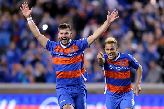 FC Cincinnati defender Forrest Lasso (3), left, and FC Cincinnati midfielder Kenney Walker (6) point to FC Cincinnati Spencer Richey (18) after winning 6-5 on penalty kicks during a USL soccer playoff game between Nashville SC and FC Cincinnati,Saturday, Oct. 20, 2018, at Nippert Stadium in Cincinnati. FC Cincinnati won 6-5 on penalties.