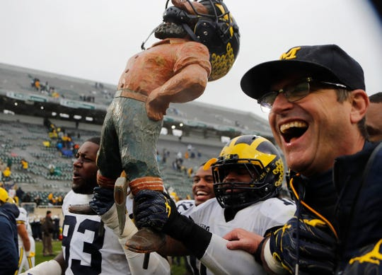 Michigan's Devin Bush, center, Lawrence Marshall (93), and coach Jim Harbaugh walk off the field with the Paul Bunyan Trophy, after defeating Michigan State, 21-7, Saturday, Oct. 20, 2018, in East Lansing.