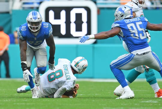 Dolphins quarterback Brock Osweiler is sacked by Lions linebacker Jarrad Davis, as defensive end Romeo Okwara celebrates in the fourth quarter.